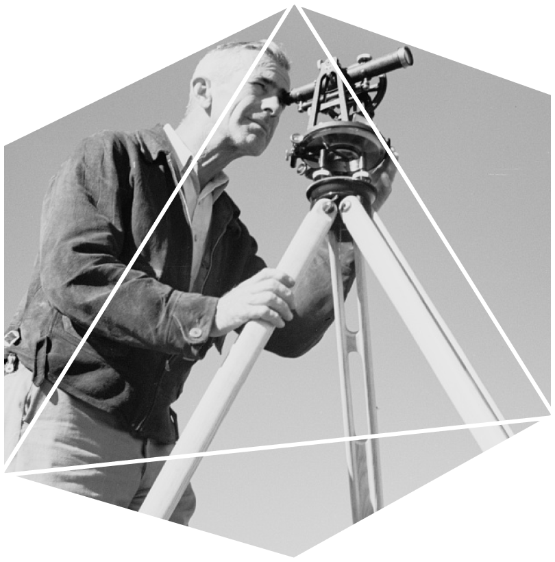 A vintage black and white photograph of a man in the 1940s using a traditional device with an optical scope component to survey land & property.