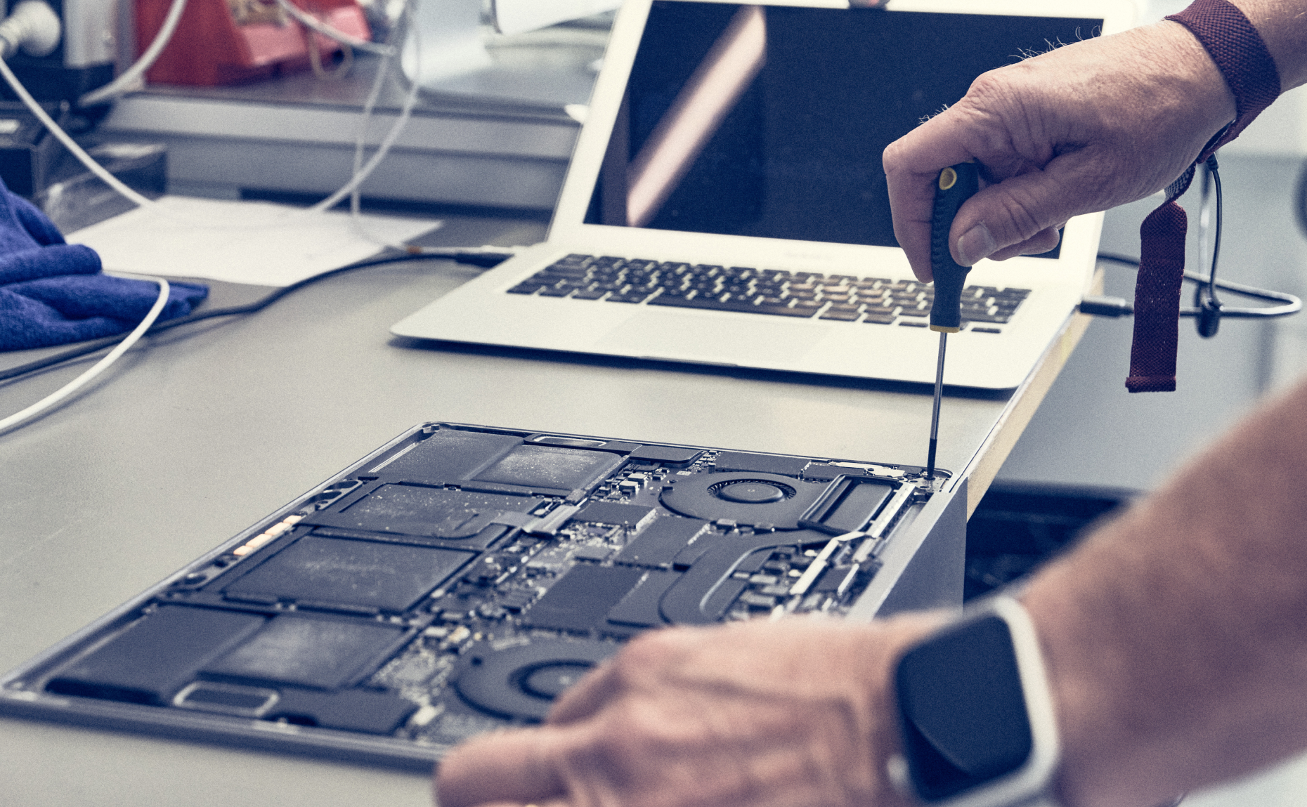 A macOS technician works on a MacBook.