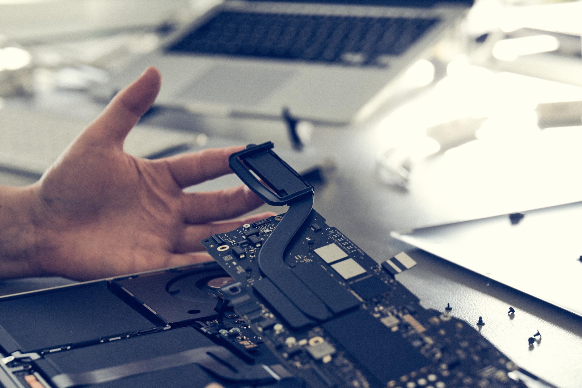 A repair technician works on an Apple MacBook.