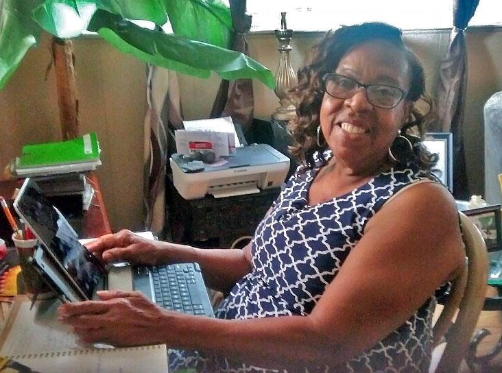 A woman with an iPad enjoying the Digital Inclusion program.