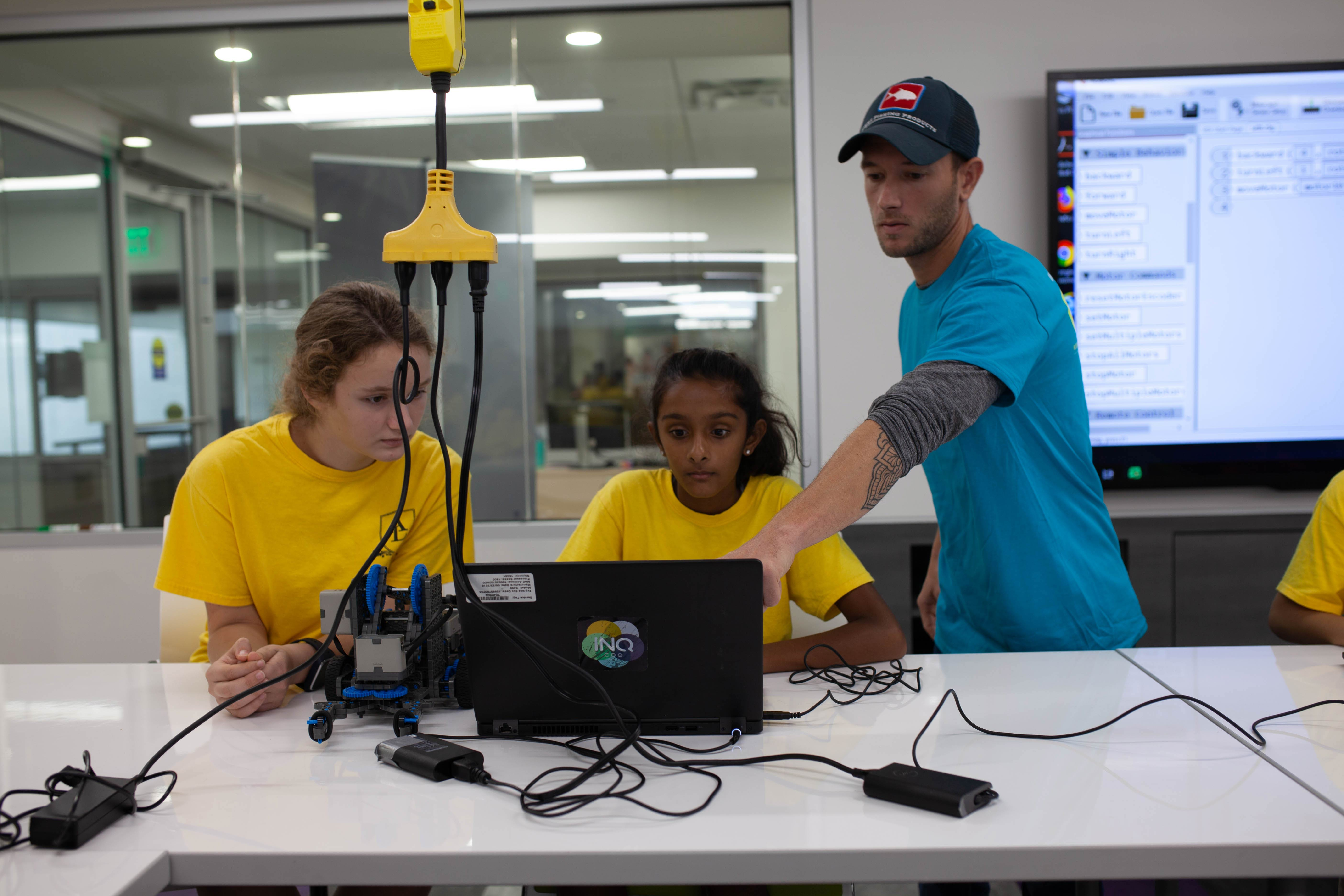 Two students with an instructor exploring STEM related technology at the SPID Science Festival