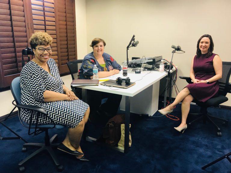 Three women talking around a desk