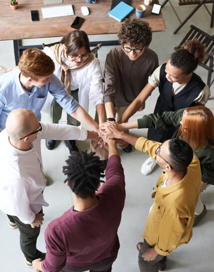 Group of people huddled in a circle with their hands stacked in the center