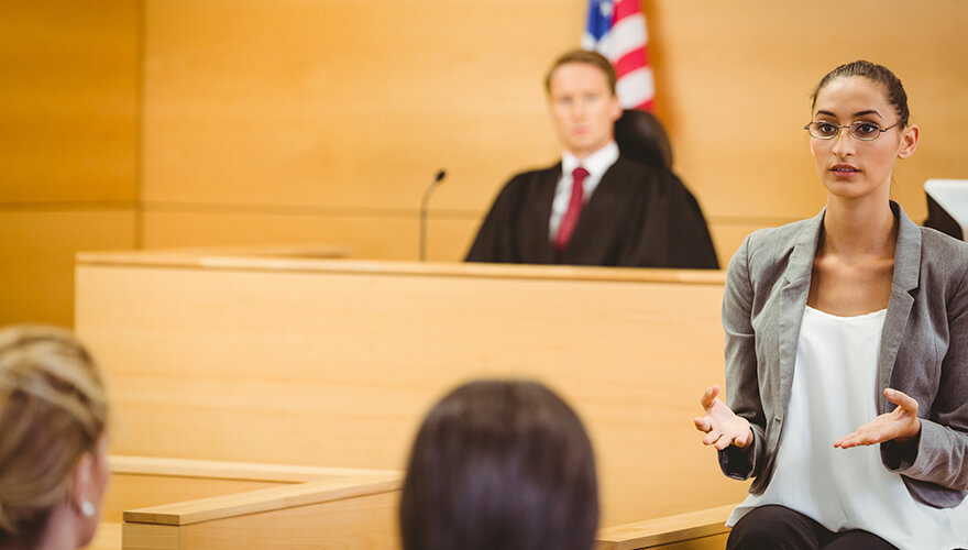 Woman using sign language in front of a judge in a courtroom