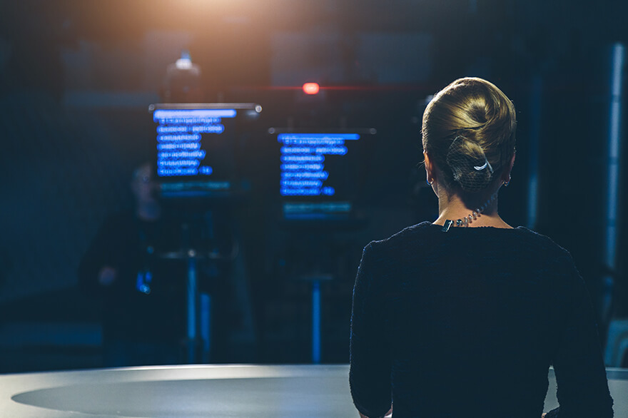 Woman behind a desk looking at two teleprompter screens