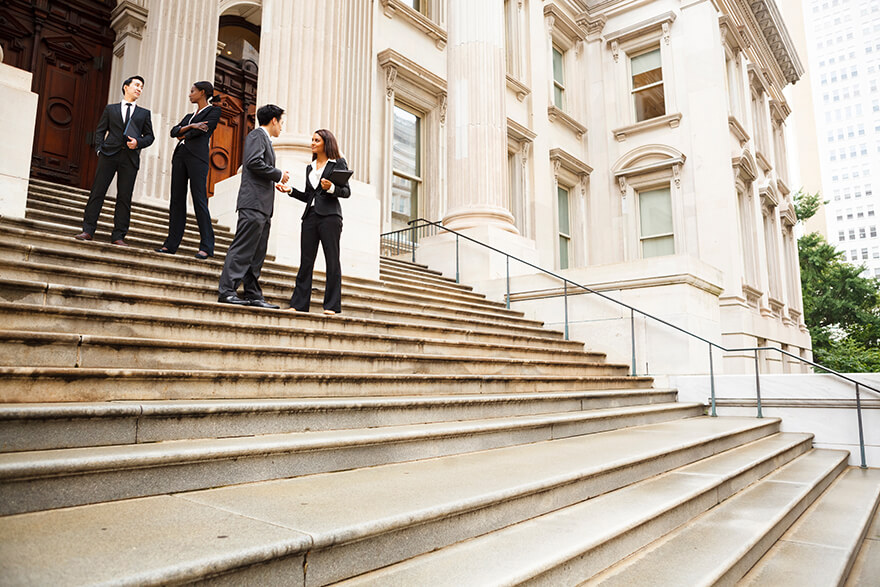 People talking at the top of stairs leading to the front of a building