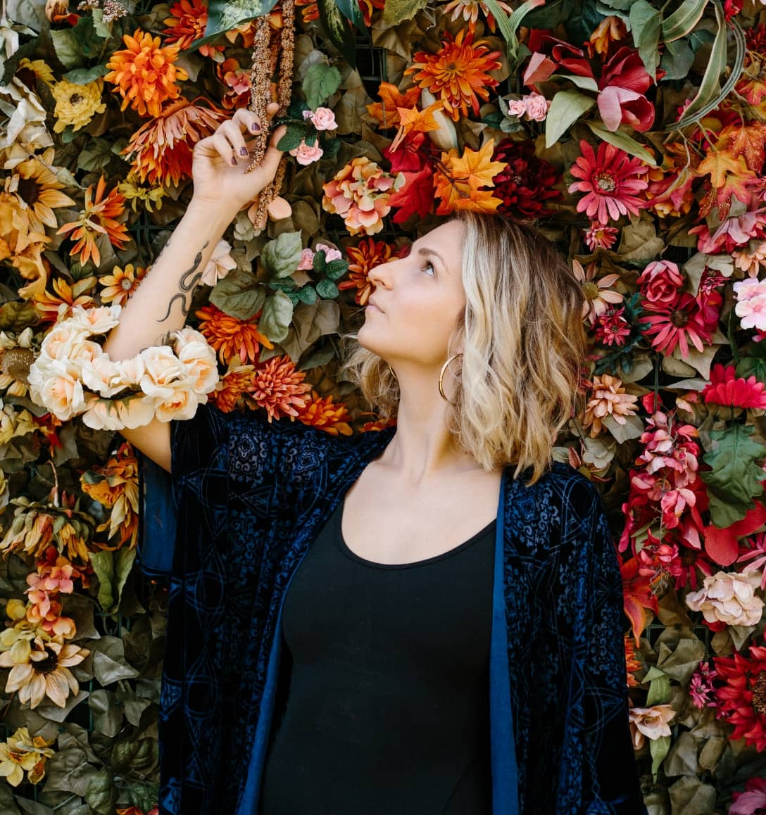 Portrait of Francesca in front of a wall of flowers