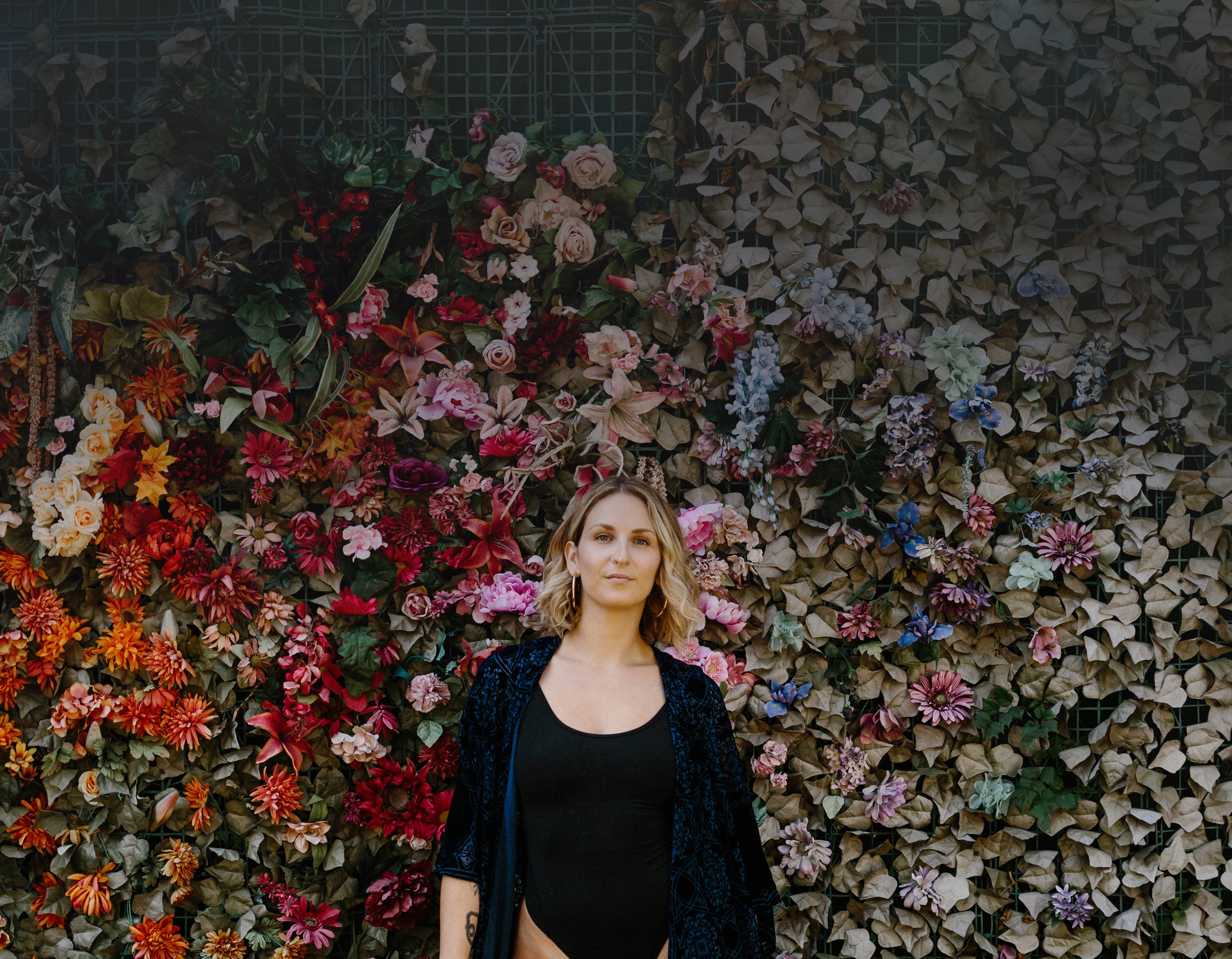 Francesca standing in front of a large flower and greenery wall