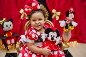 Girl dressed like Minnie Mouse holding a plushie