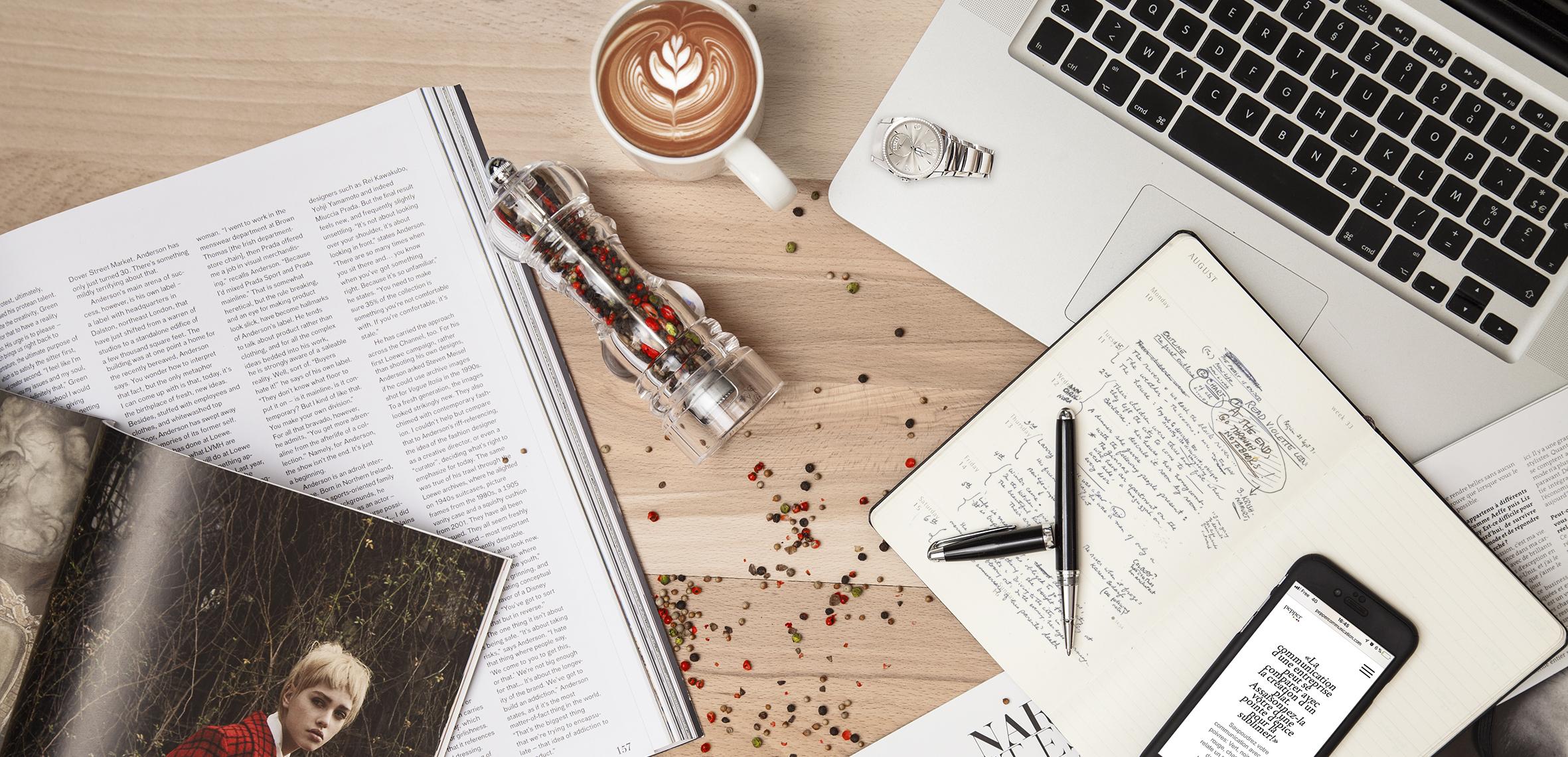 Un cahier, une montre, un magazine, un téléphone et un poivrier poser sur une table avec des grains de poivres dispersés.