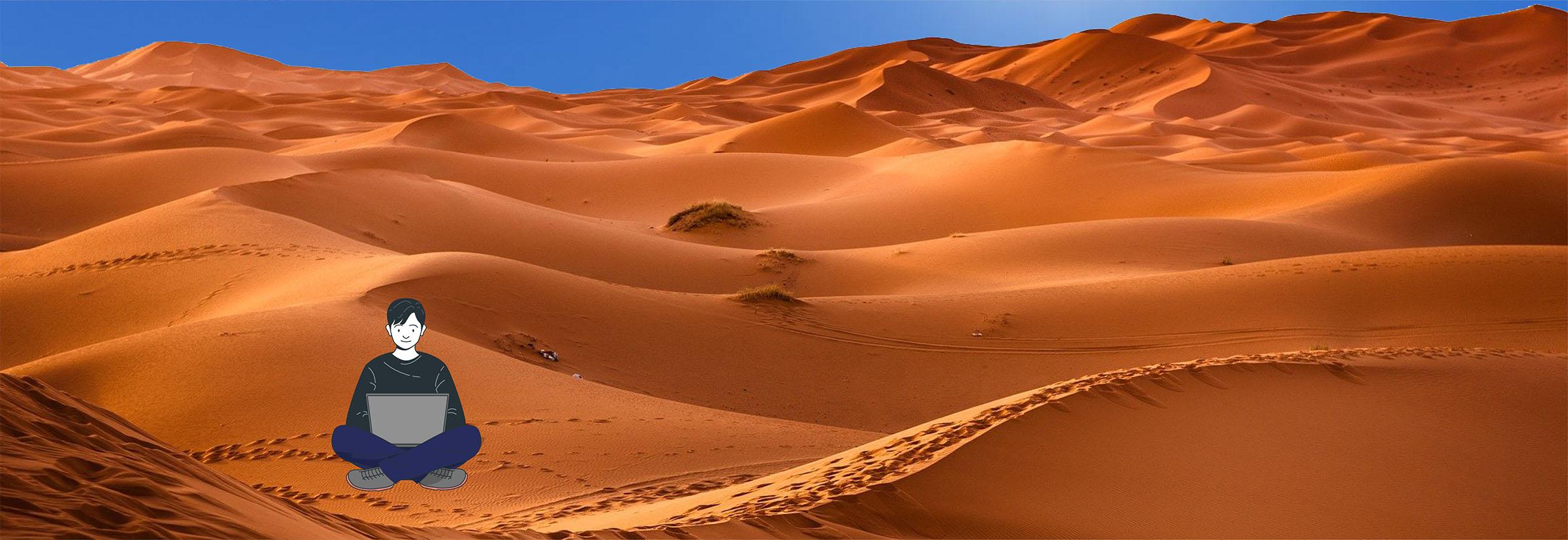 Digital nomad travaille sur son ordinateur portable dans les dunes du désert du Sahara
