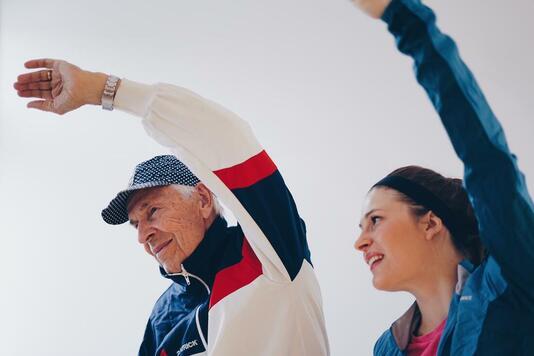 gubbe employee and elderly raising hands