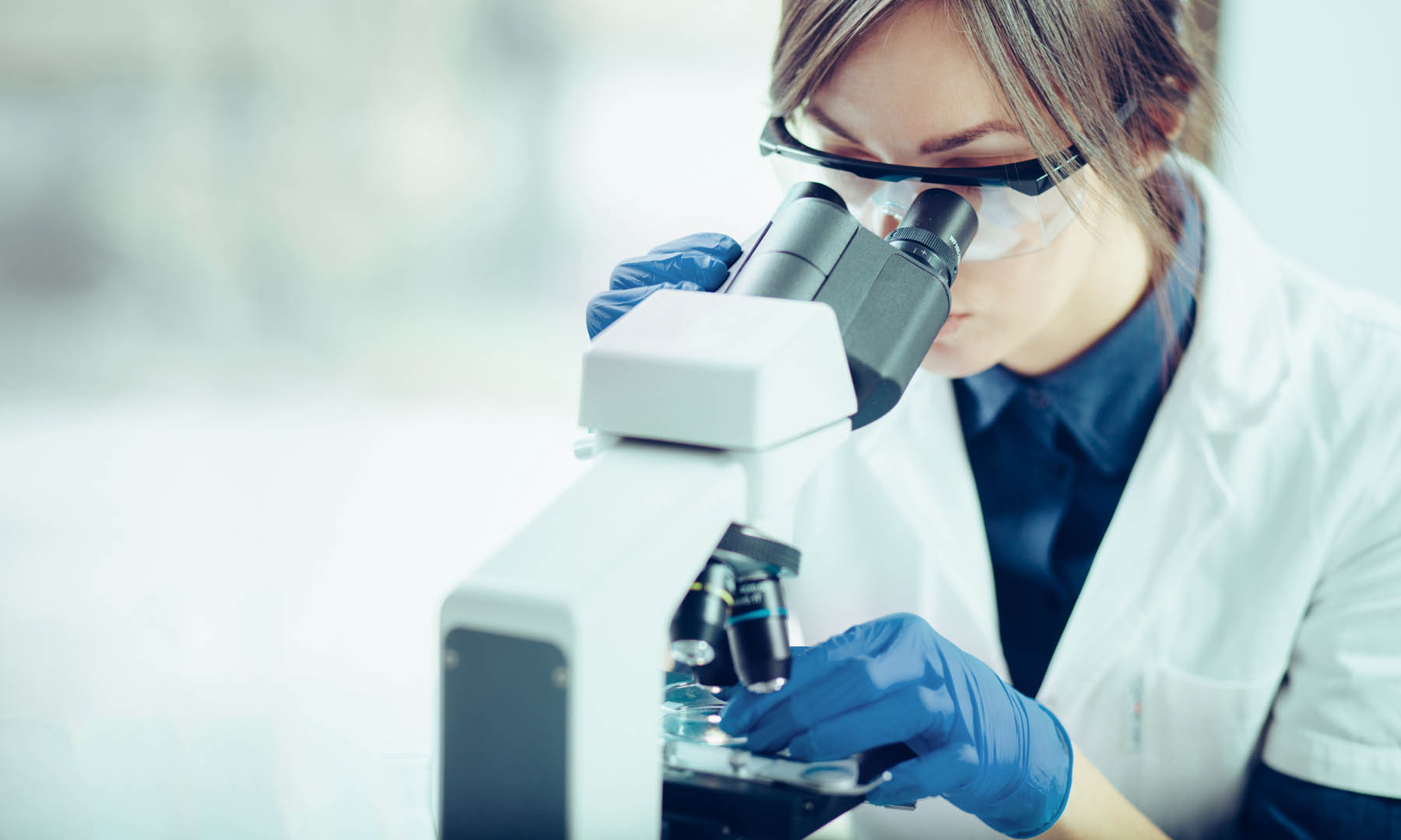 Picture of a scientist looking through a microscope.