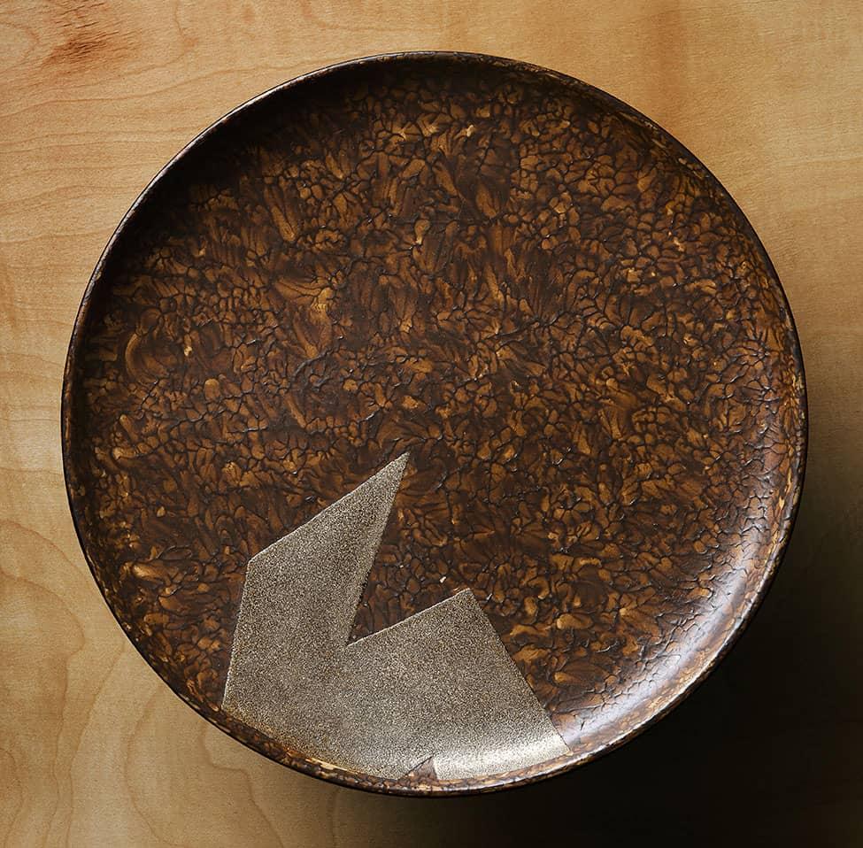 Assiette en laque arrachée brune et décor géométrique argent