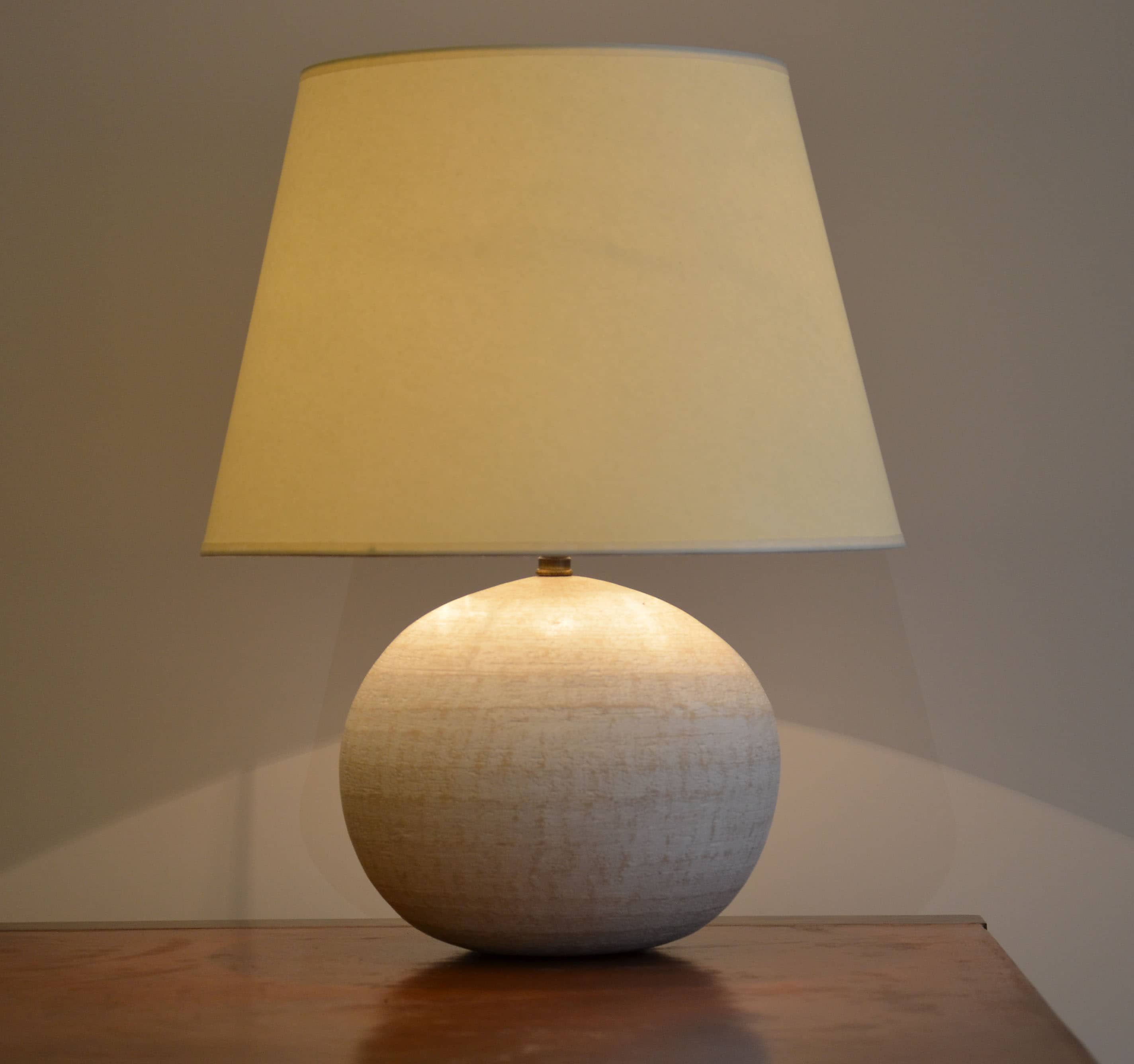 Lampe boule aplatie en terre cuite recouverte de plâtre.