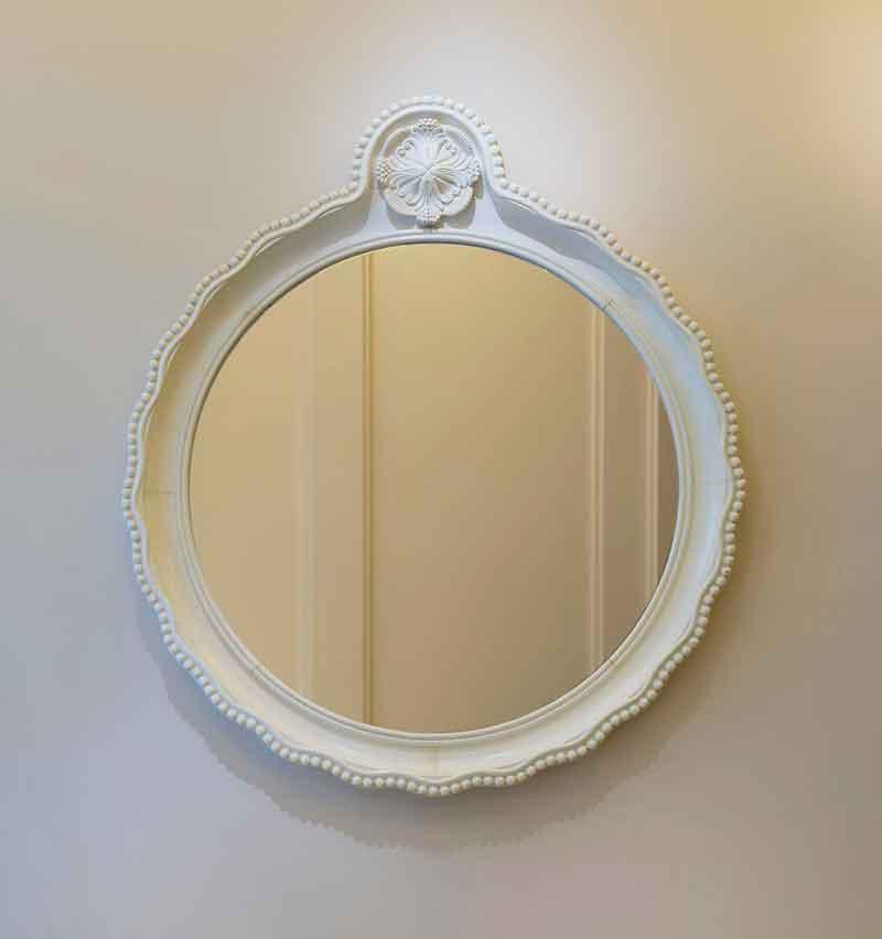 Miroir circulaire en bois laqué blanc perlé. La bordure chantournée surmontée d'une fleur stylisée.