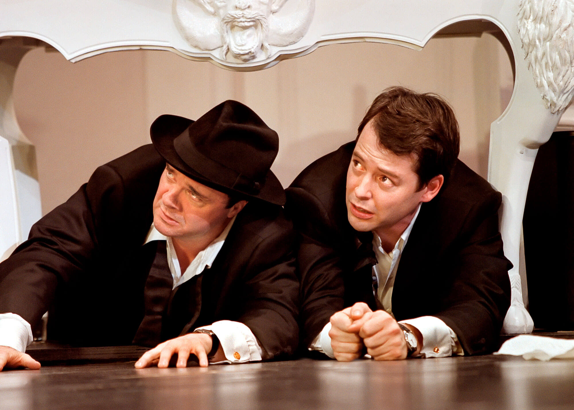 Nathan Lane and Matthew Broderick hiding under a white table. They look worried.