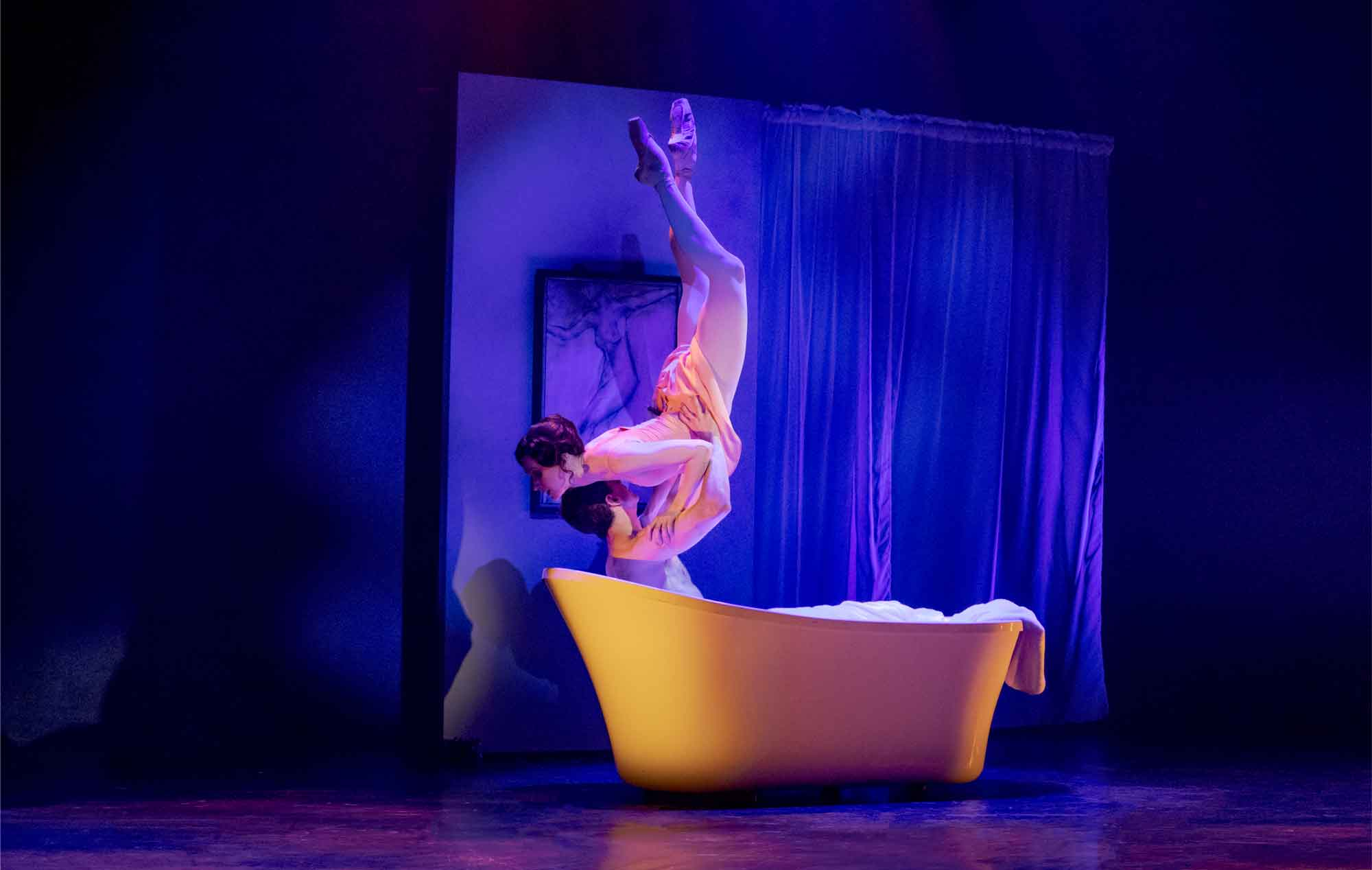 Woman suspended in an upside down lift in a bathroom. Male partner is lying in the tub and holding her in the air. There is dim lighting.