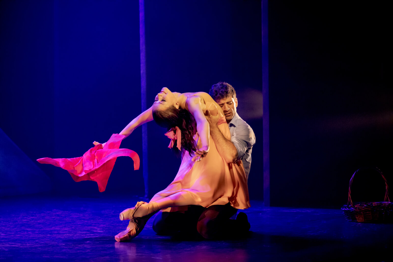 Tony Yazbeck and Irina Dvorovenko in a pas de duex: the man is kneeling and hugging woman in a backbend. She is holding a red scarf.