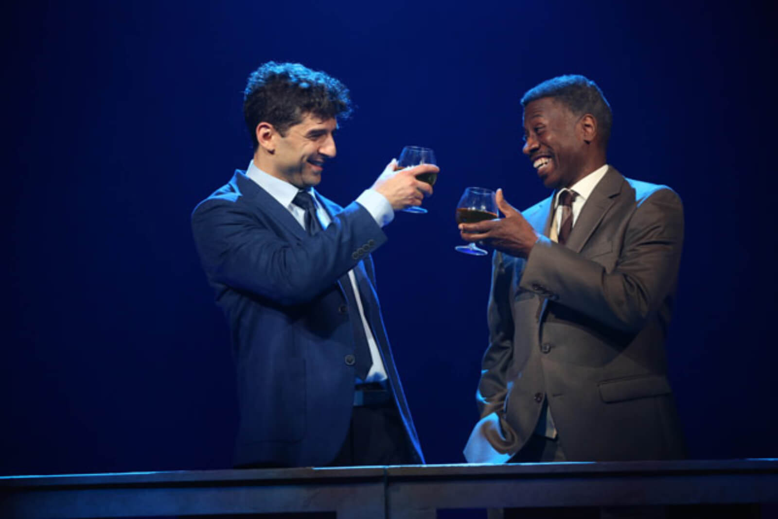 Two men, played by Tony Yazbeck and Teagle F. Bougere, clink glasses.