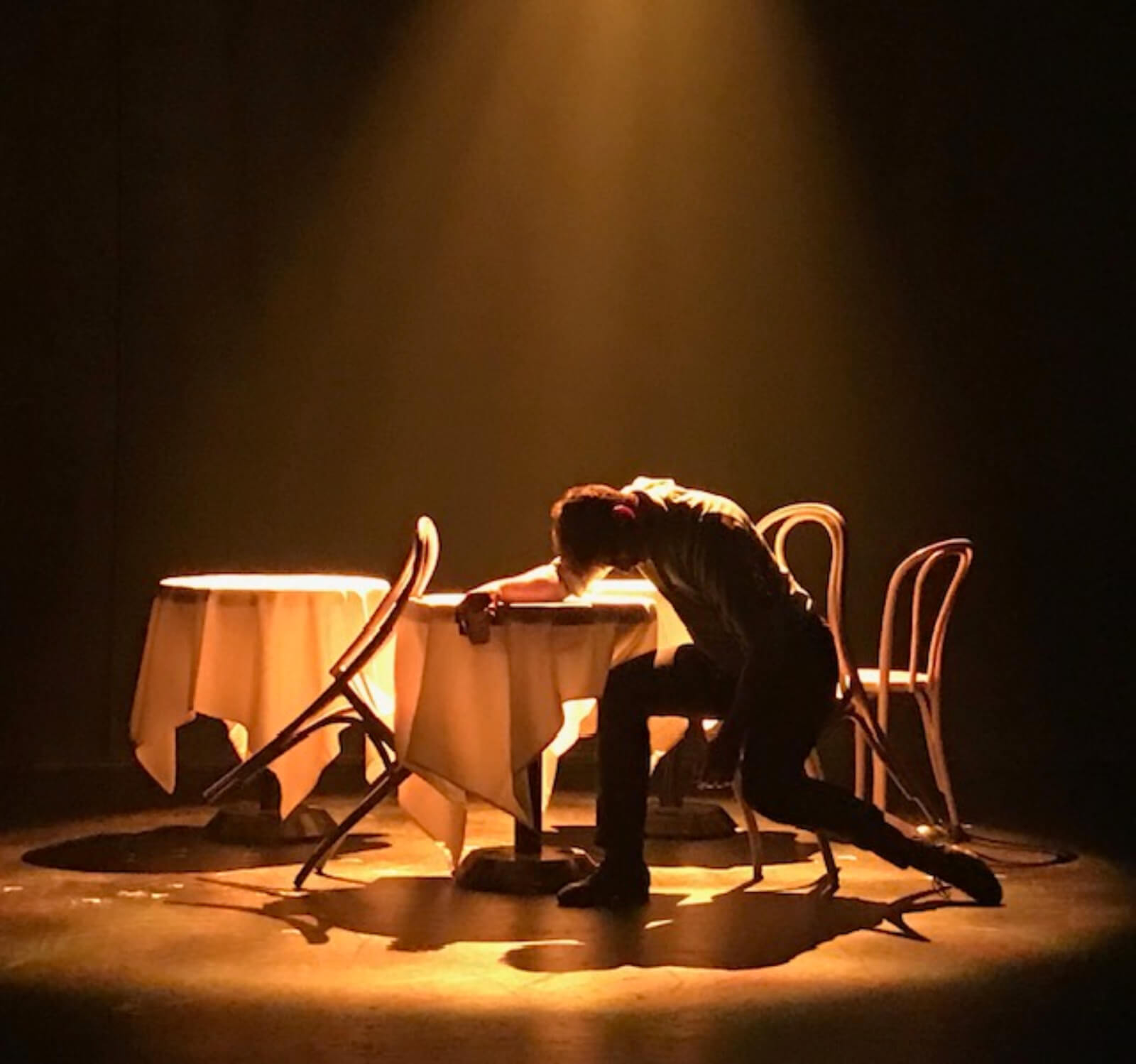 """John Marcher played by Tony Yazbeck in the """"Waltz Melancolique"""" scene from The Beast in the Jungle. Tony Yazbeck hunched over a table in dim lighting."""