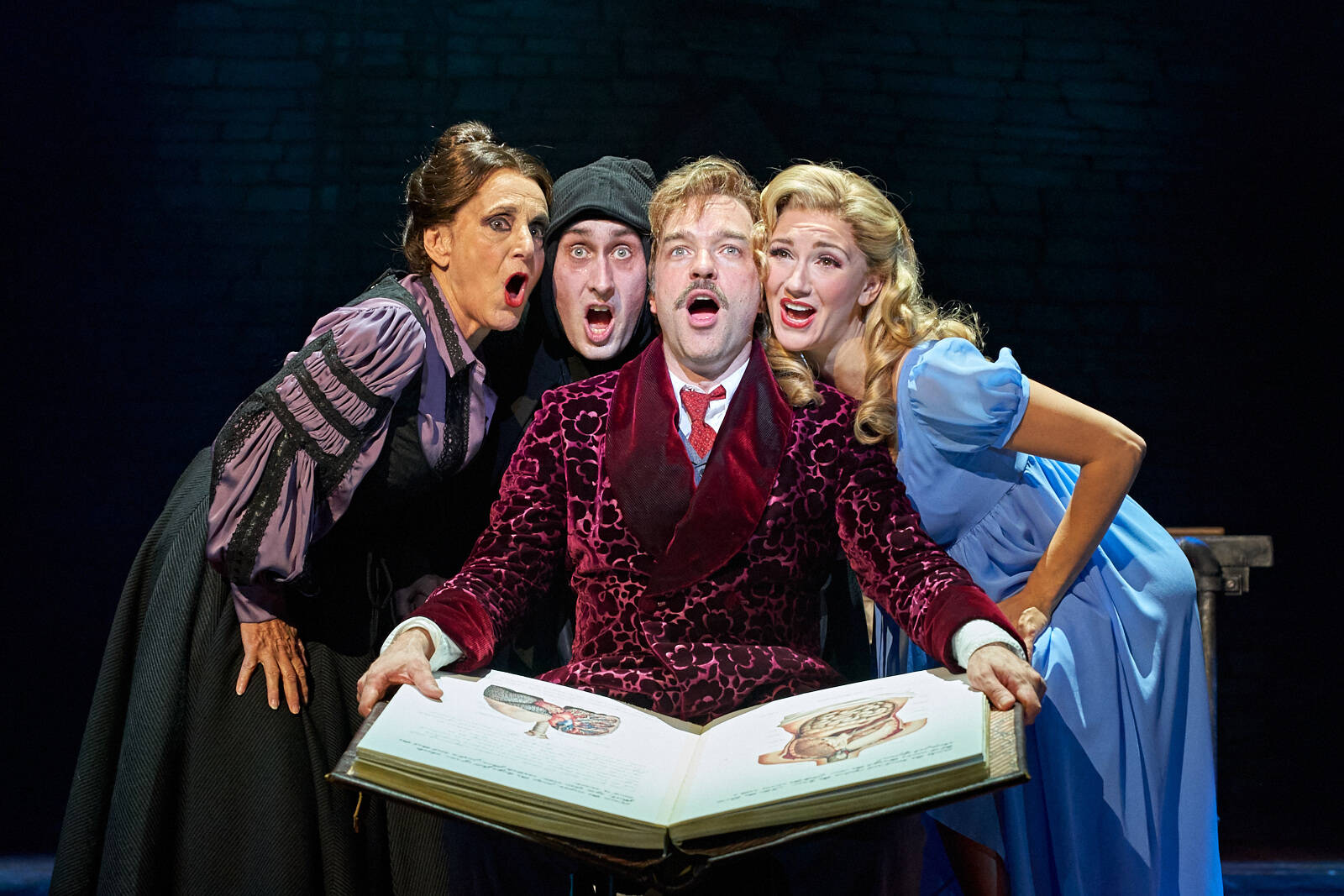 """Frau Blucher (Lesley Joseph), Igor (Ross Noble), Dr. Frankenstein (Hadley Fraser) and Inga (Summer Strallen) singing """"It Could Work"""". They sing around a science book called HOW I DID IT!"""