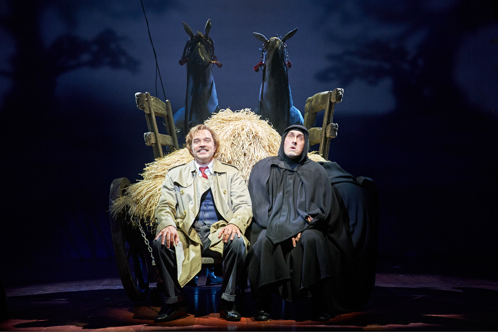 """Sitting in a horse drawn carriage full of hay, Dr. Frankenstein (Hadley Fraser) and Igor (Ross Noble) smile as they finish singing the number """"Together Again""""."""