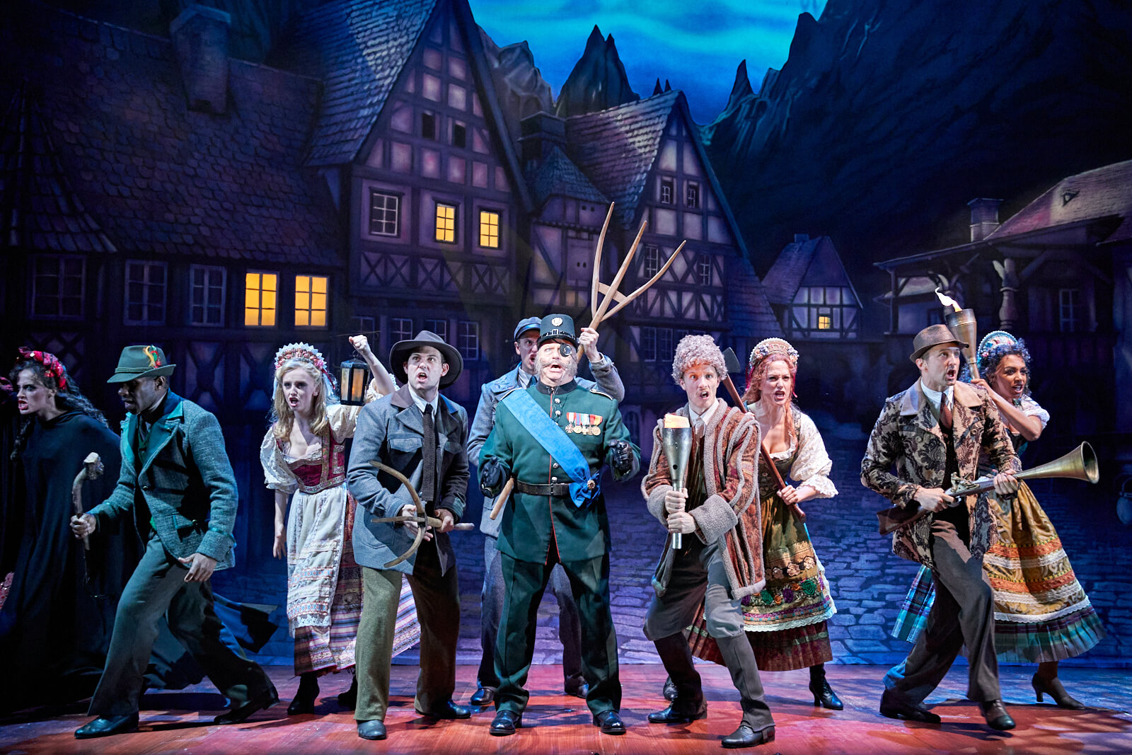 """Inspector Kemp (Patrick Clancy) sings """"Hang Him Til He's Dead"""" with the angry villagers of Transylvania backing him up with various weapons."""