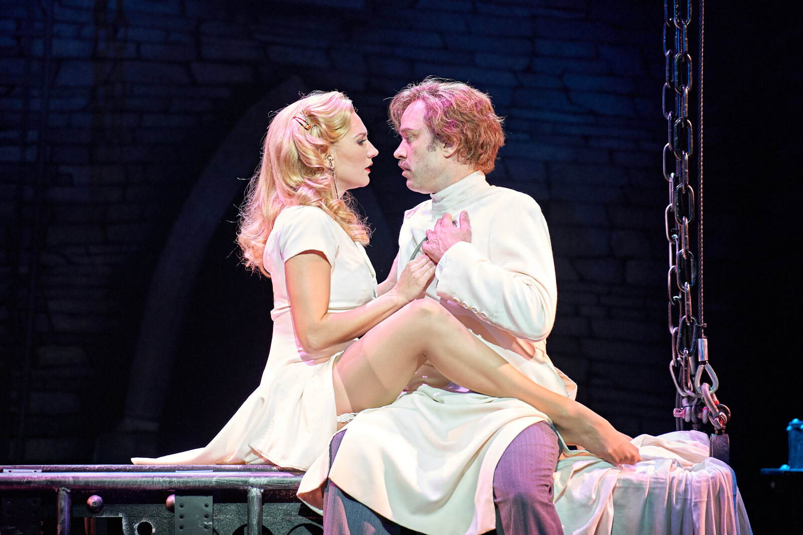 """Inga (Summer Strallen) sings """"Listen to Your Heart,"""" to Dr. Frankenstein (Hadley Fraser) sitting on a lab table. She has her hand on his heart."""