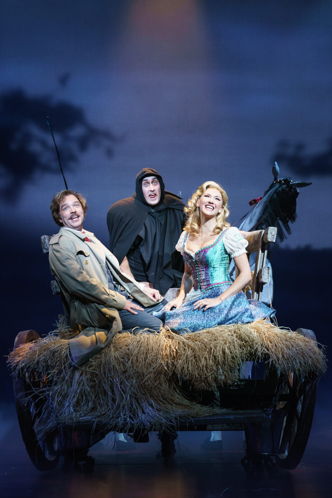 """Dr. Frankenstein (Hadley Fraser), Igor (Ross Noble), and Inga (Summer Strallen) sing """"Roll in the Hay,"""" having a good time at the back of a horse-drawn carriage full of hay."""