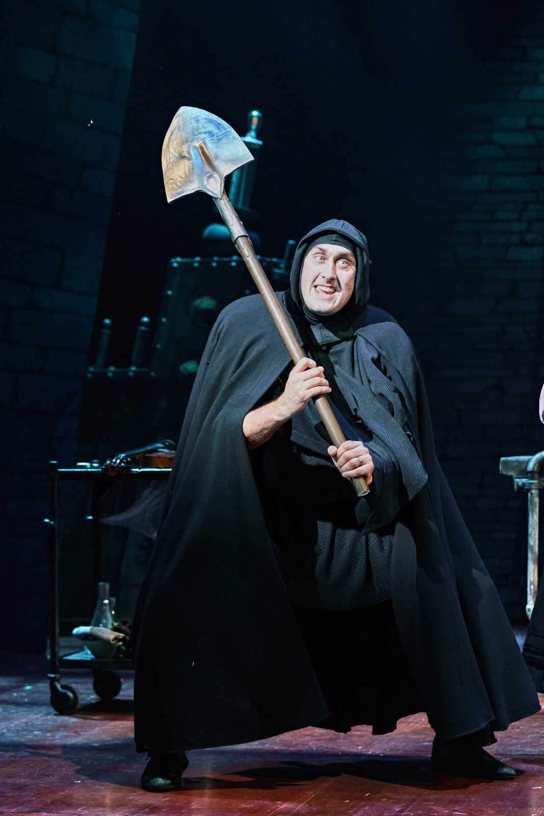 """Igor (Ross Noble) sings """"It Could Work"""" while holding a shovel with the intention of digging up a corpse for Dr. Frankenstein."""