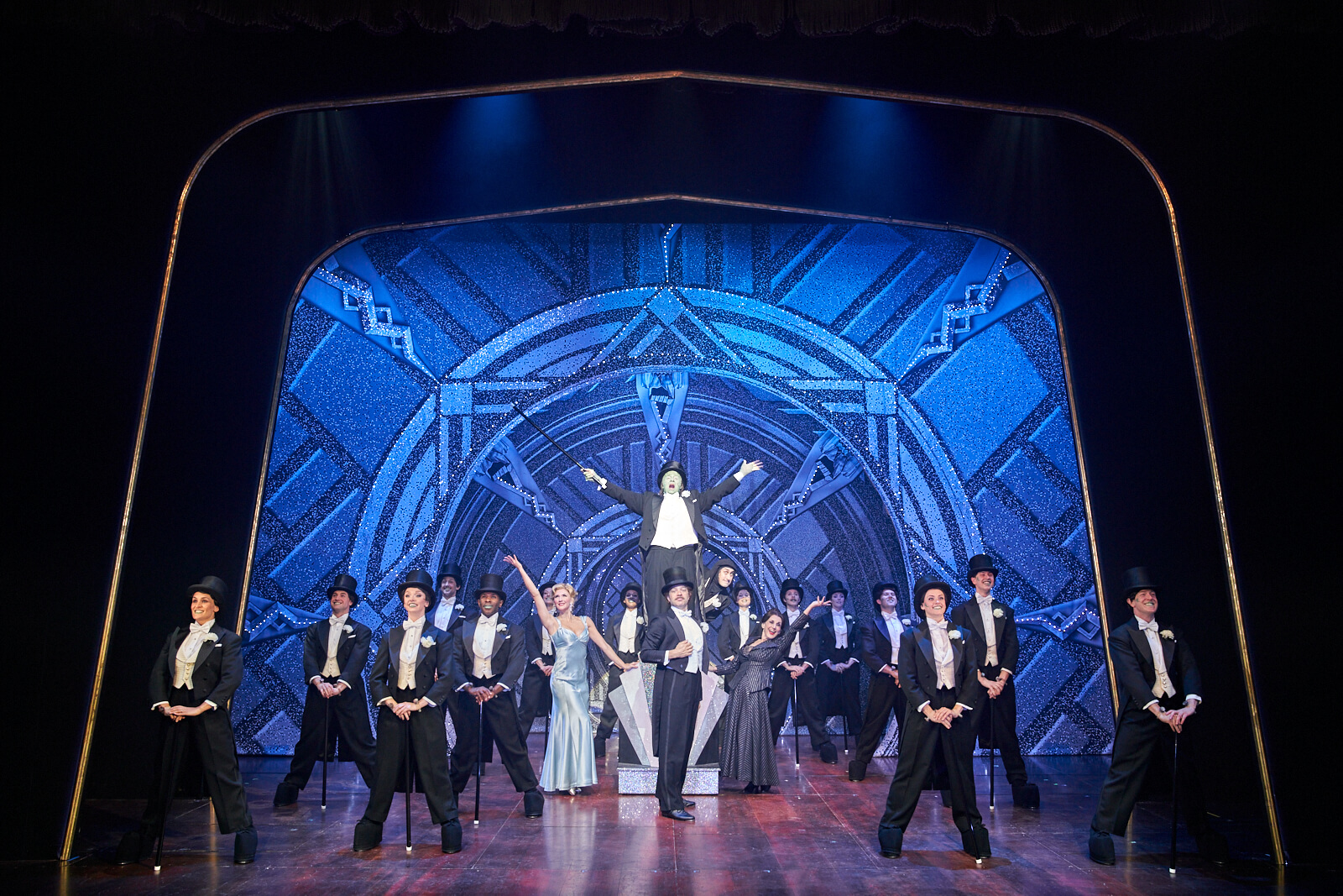 """The Monster (Nic Greenshields) standing on a pedestal, hits a full picture pose of """"Puttin on the Ritz"""" with Inga, Dr. Frankenstein, Igor, Frau Blucher and the ensemble."""