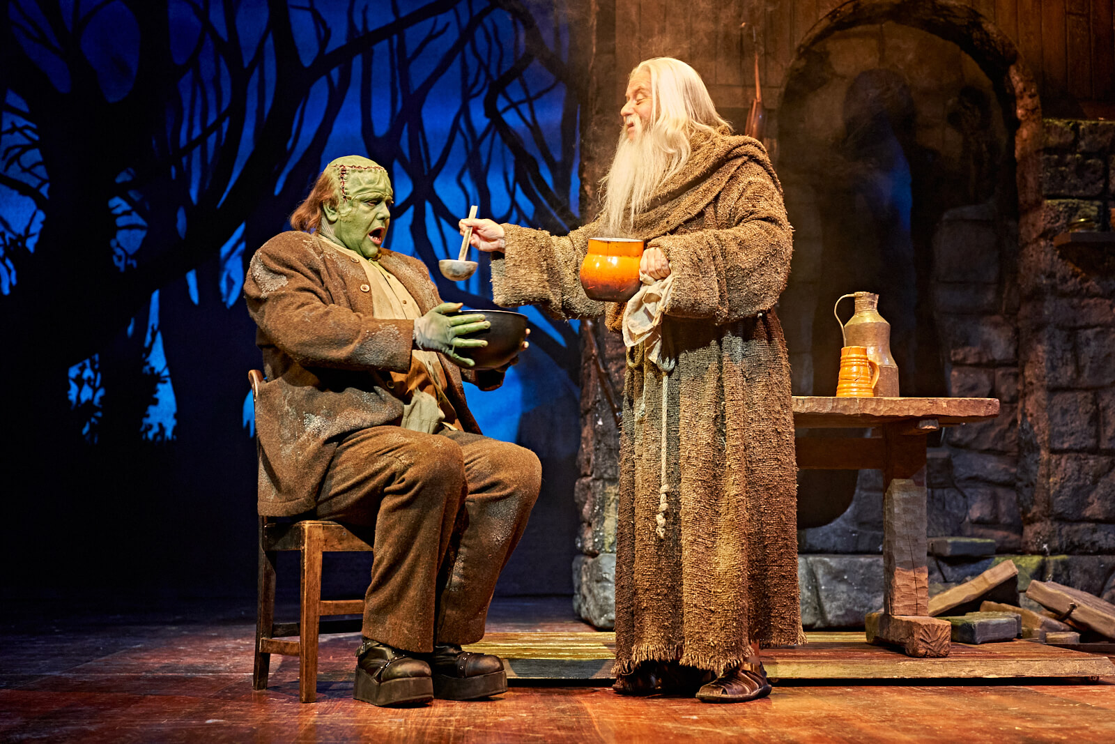 The Hermit (Patrick Clancy) serves his new friend, The Monster, some hot soup.