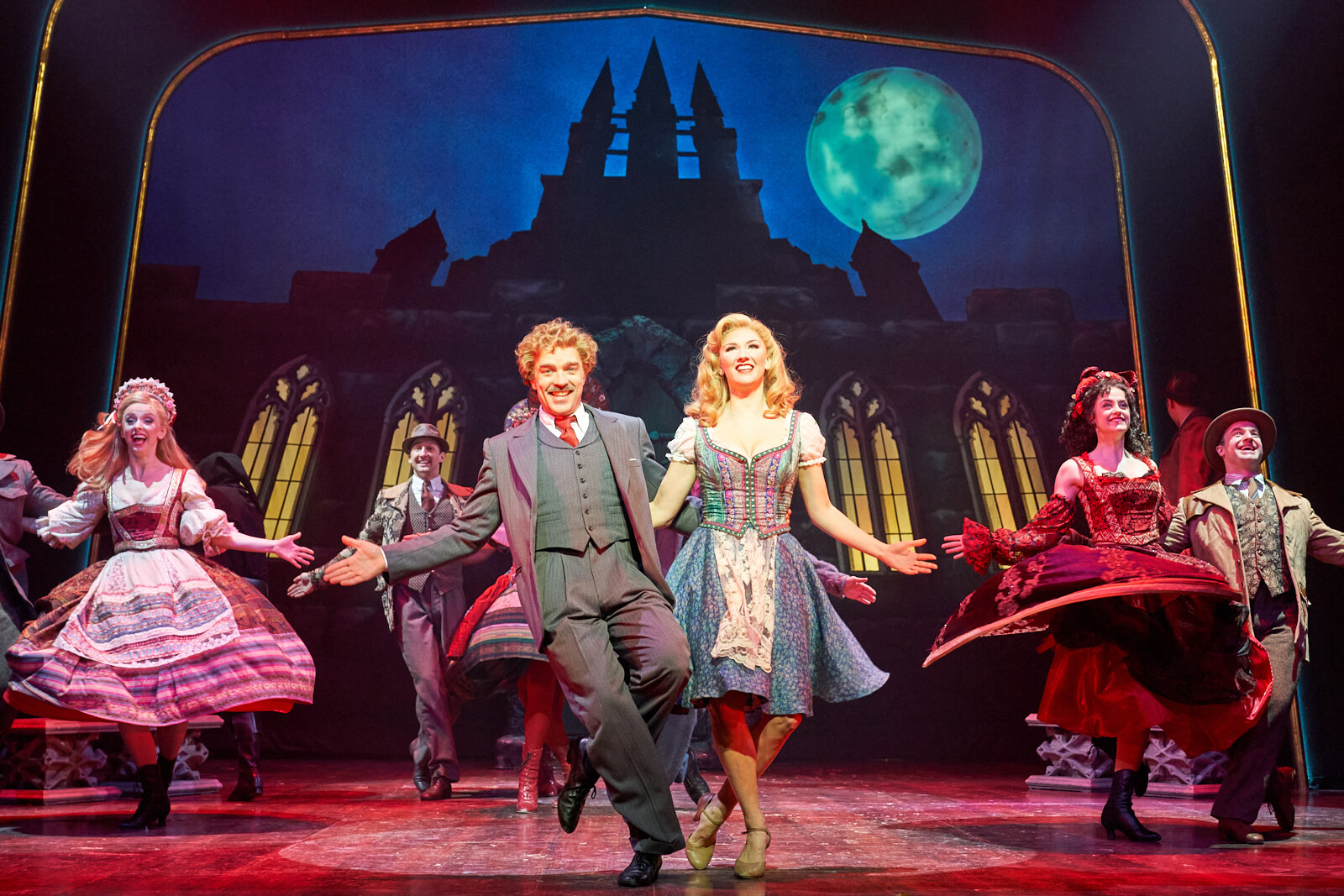 """Dr. Frankenstein (Hadley Fraser) and Inga (Summer Strallen) happily dancing under a full moon in front of the castle with The Villagers to the song """"Transylvania Mania"""" in Young Frankenstein West End."""