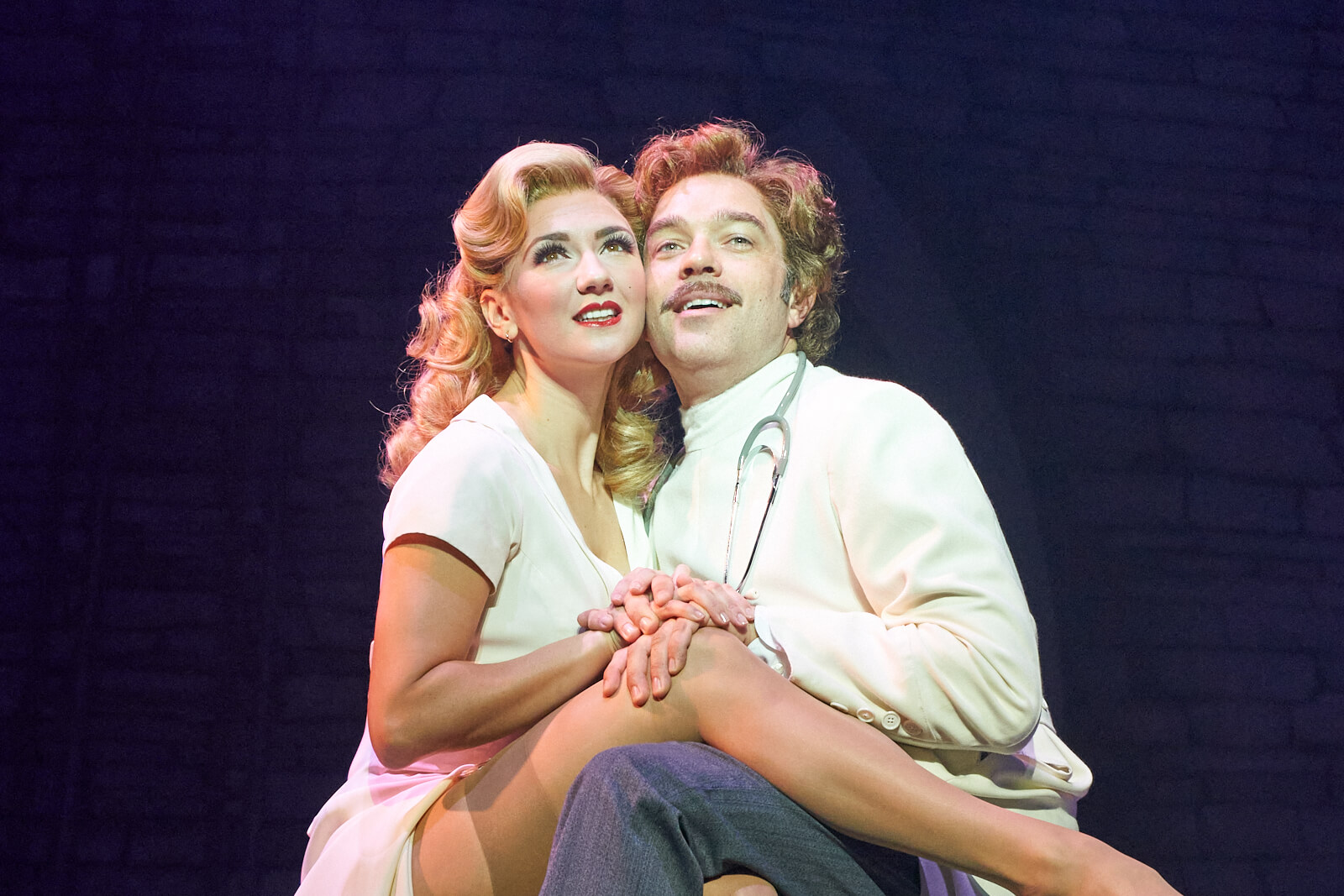 """Inga (Summer Strallen) and Dr. Frankenstein (Hadley Fraser) singing """"Listen to Your Heart"""" sitting on the lab table in Young Frankenstein (West End)."""