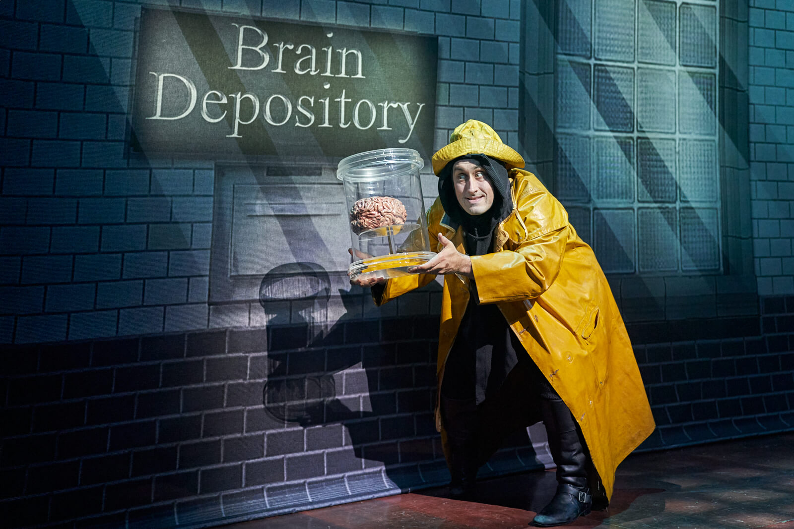 Igor (Ross Noble) in a yellow raincoat stealing a brain from a brain depository in Young Frankenstein (West End).