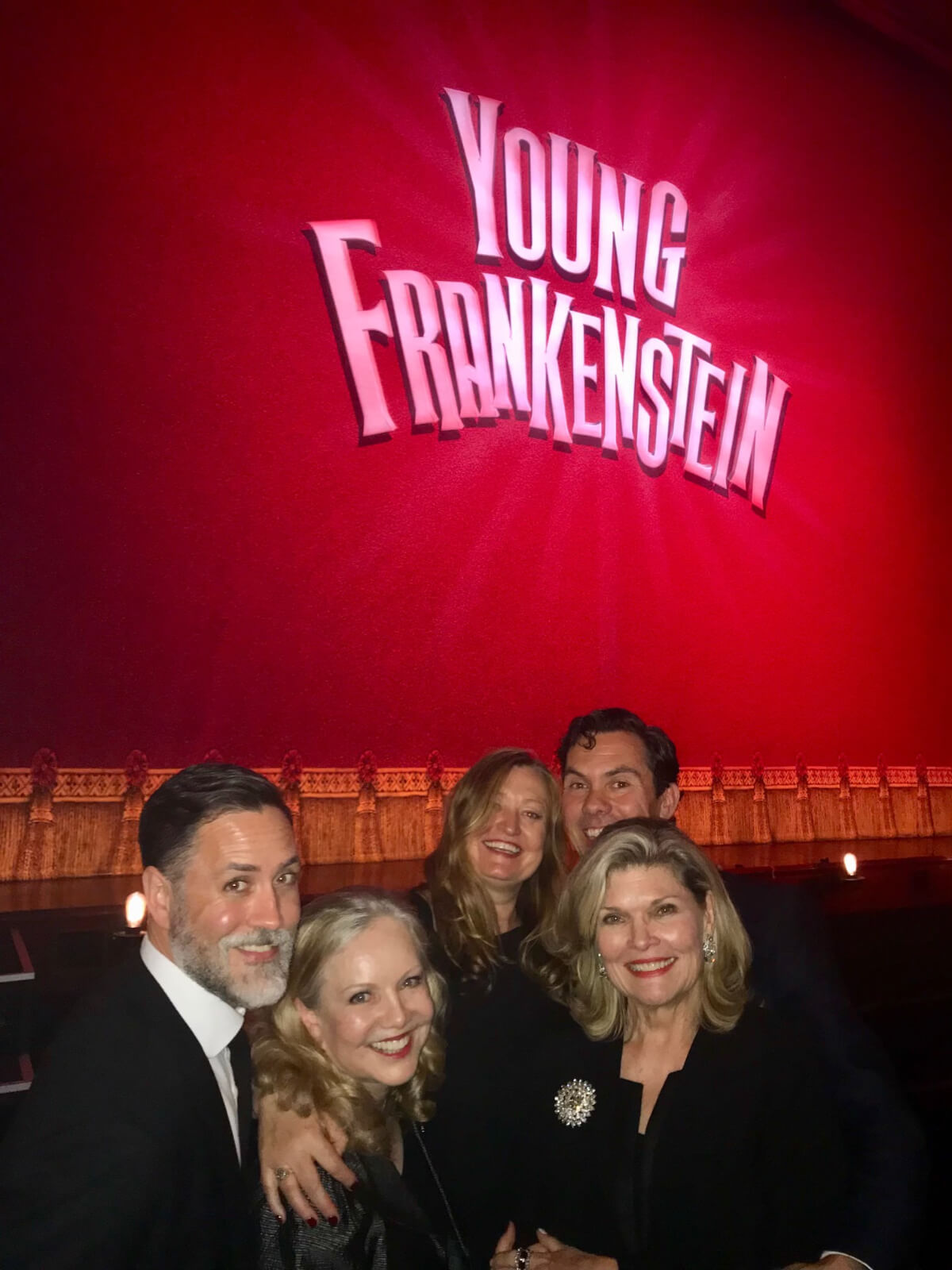 """Susan Stroman and four associates in front of the red curtain showing """"Young Frankenstein"""" in neon letters before the show starts on the West End."""