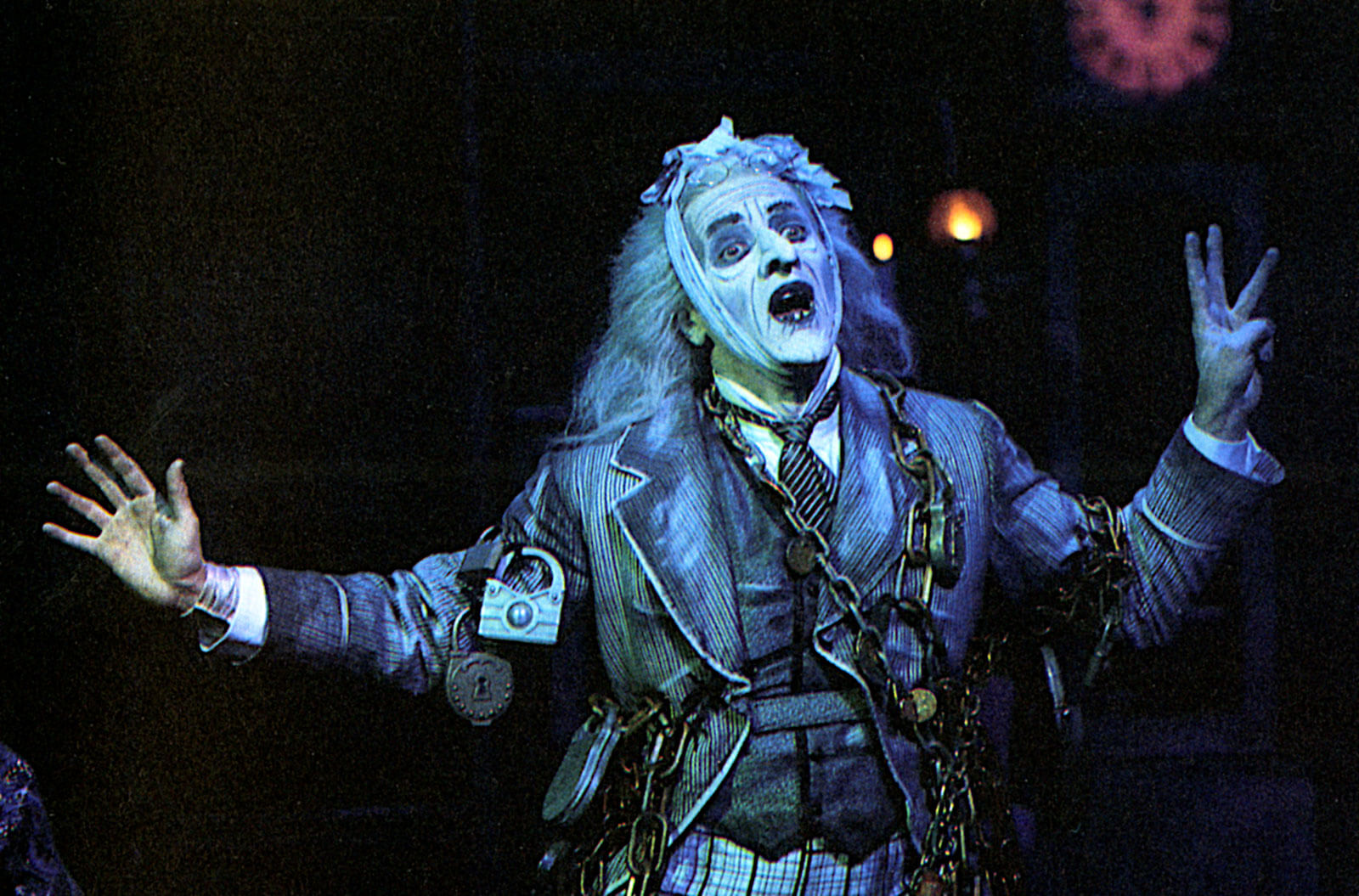 The Ghost of Jacob Marley (Jeff Keller) appears and is wrapped in chains with candlelight in the background.