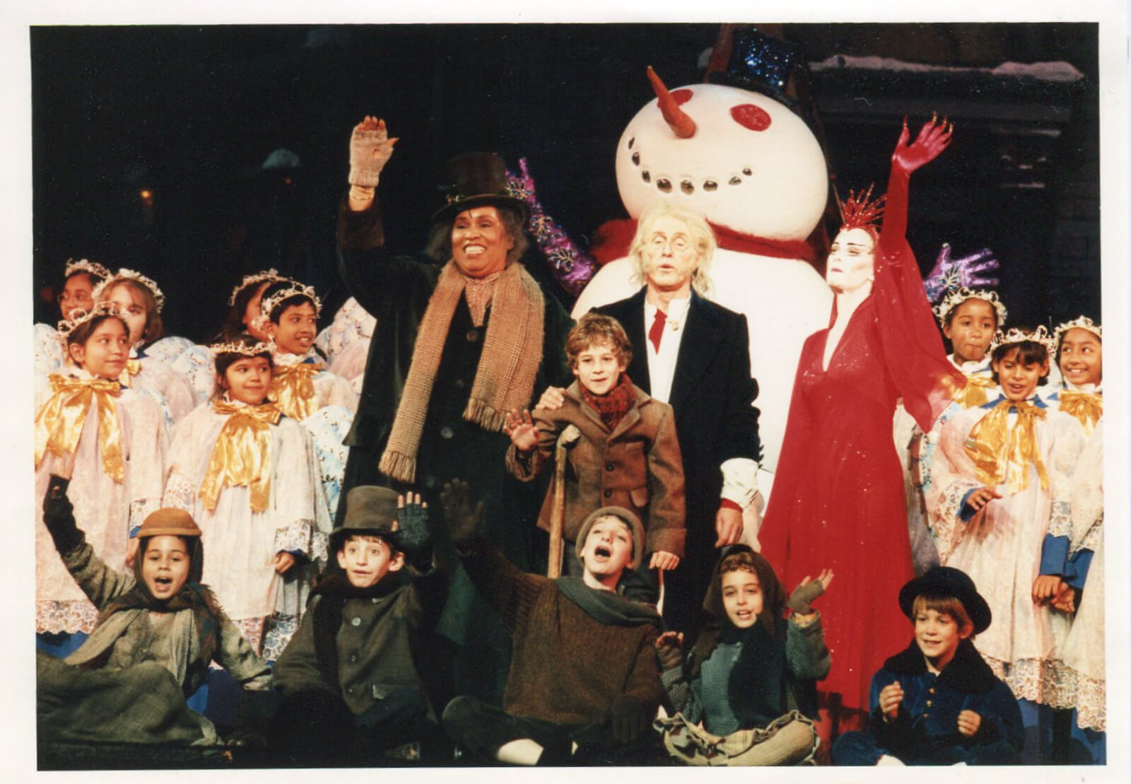 The Ghost of Christmas Present (Roz Ryan), Ebenezer Scrooge (Roger Daltry), The Ghost of Christmas Yet-to-Be (Catherine Batcheller) and company at the Curtain Call of A Christmas Carol. In front of a giant snowman.