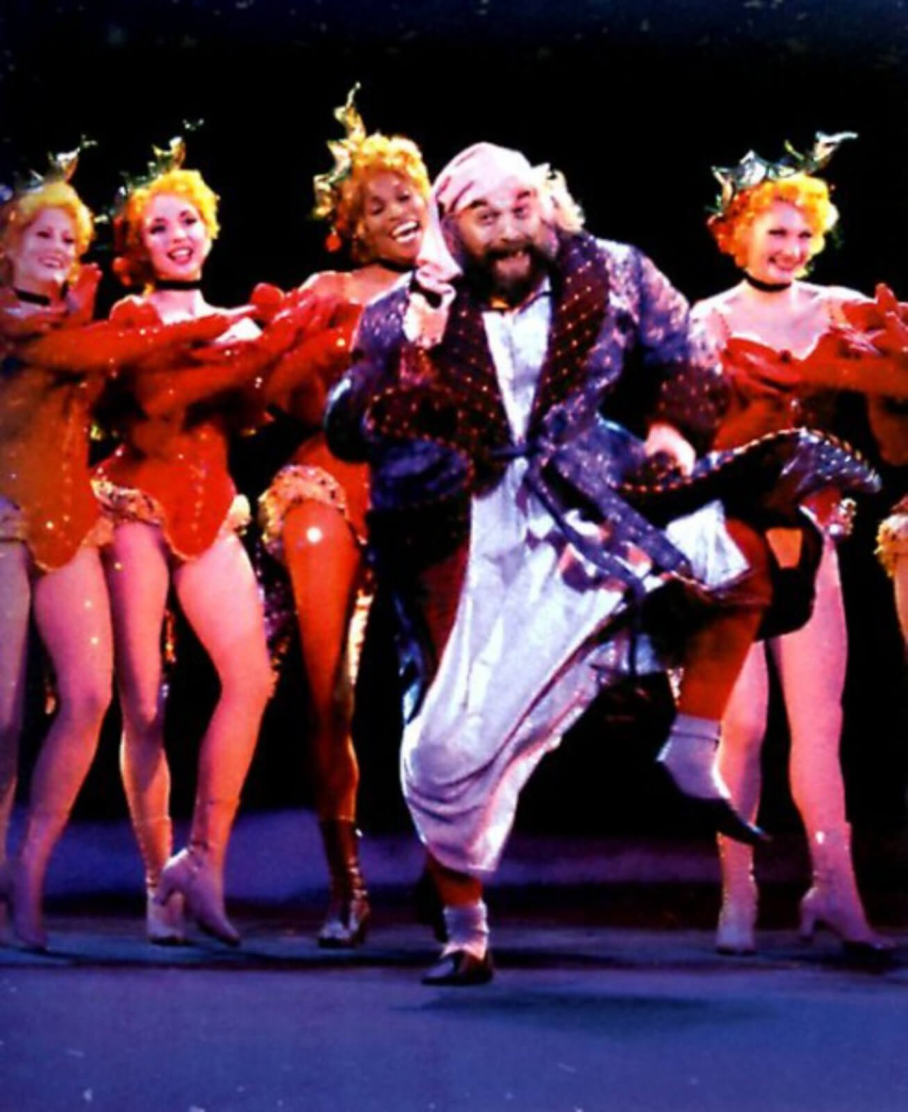 Scrooge (Walter Charles) in a robe happily dancing as he is surrounded by Holly Girls in bright red costumes