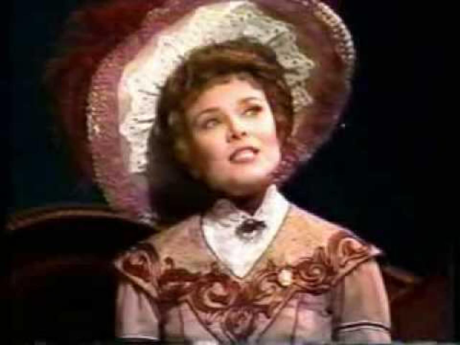 """Maureen Moore as Countess Charlotte singing """"Everyday a Little Death"""". She is wearing beautiful turn of the century hat and dress with white lace and peach embroidery."""