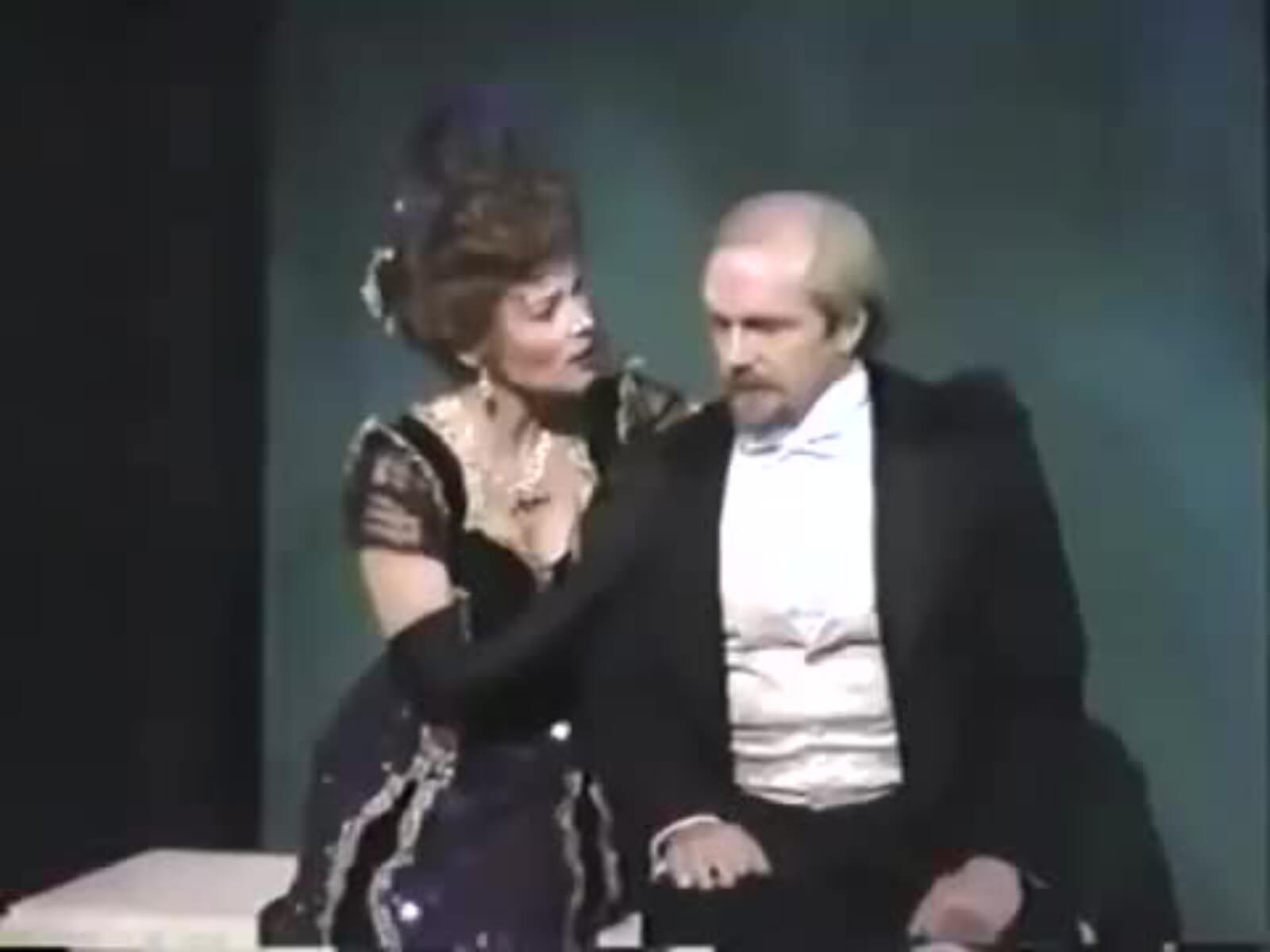 Maureen Moore as Countess Charlotte and George Lee Andrews and Frederik Egerman. Charlotte is consoling Frederik because his son ran off with his young wife. They are dressed in black tie and an elegant gown in A Little Night Music.