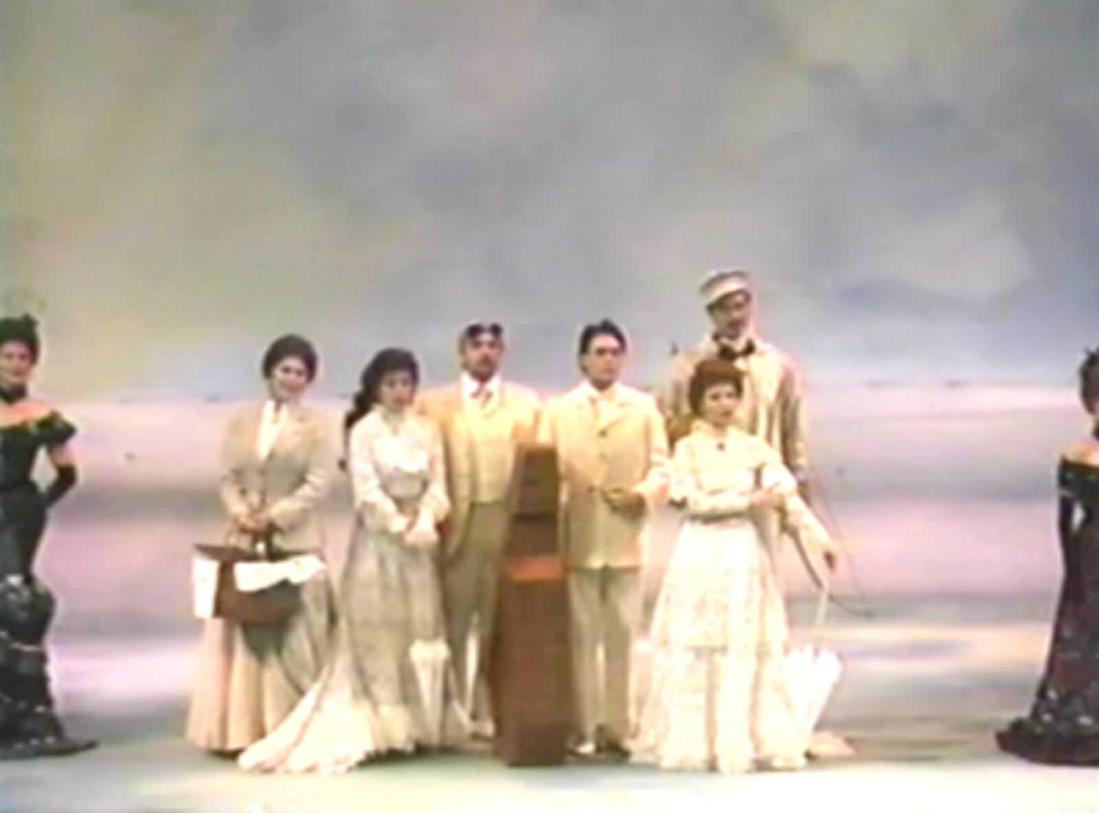 """The cast of A Little Night Music singing """"A Weekend in the Country"""". They are dressed in white traveling garb standing in front of a Monet-like background."""