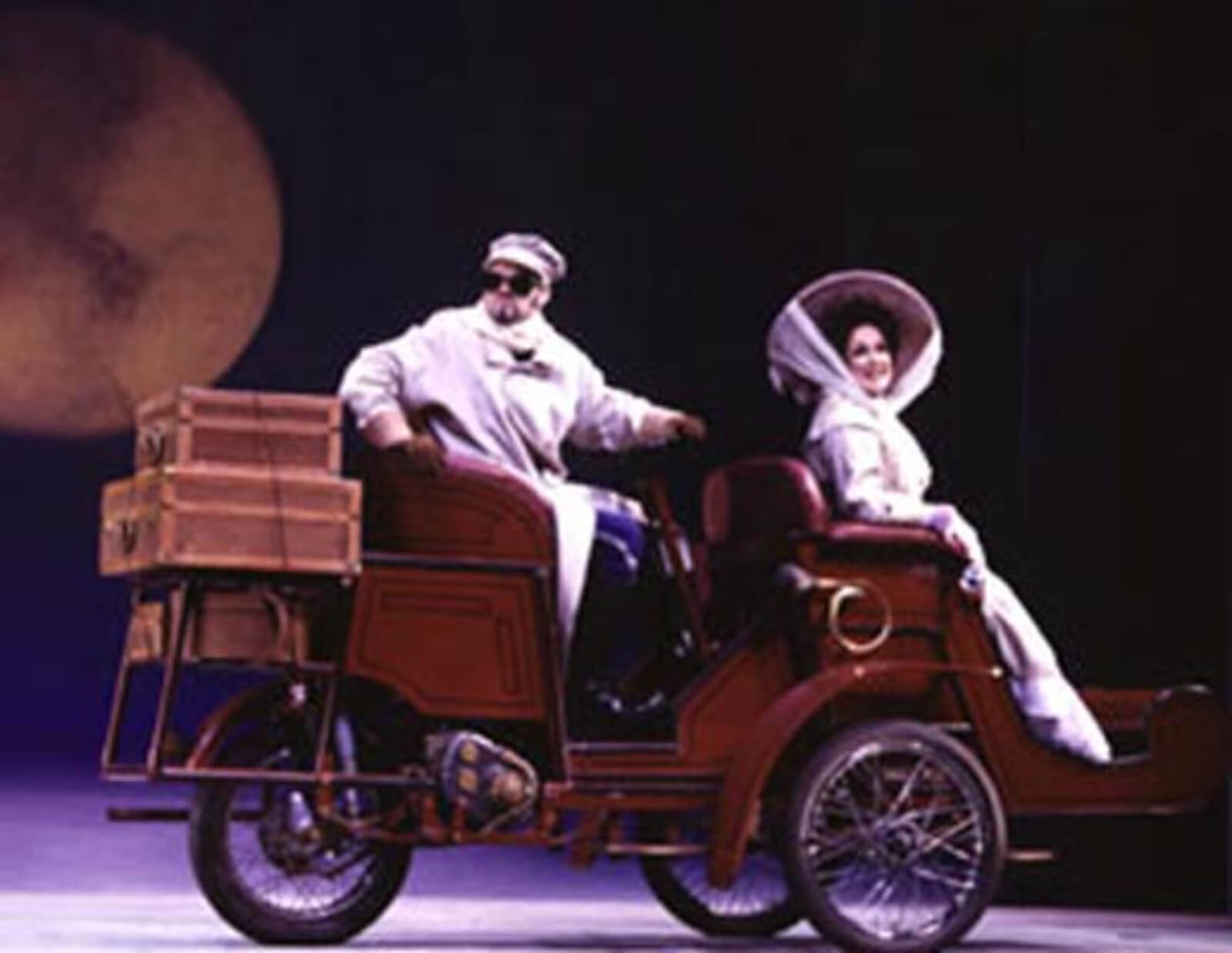 Marc Kudisch as Count Carl-Magnus driving Charlotte. He is in a long white coat and she is dressed in a white traveling gown.