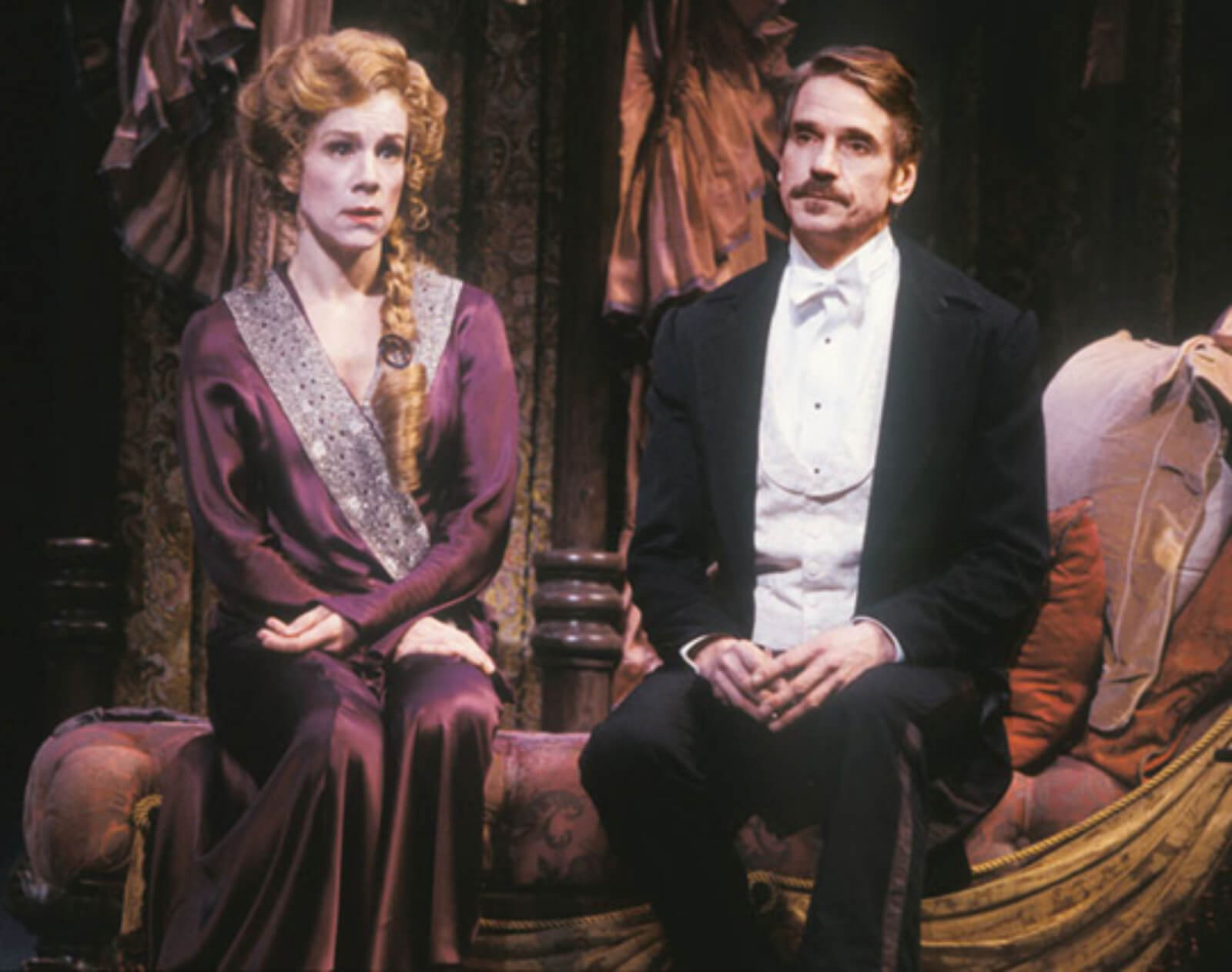 """Juliet Stevenson as Desiree Armfeldt and Jeremy Irons as Fredrik Egerman sing """"You Must Meet My Wife"""". She is dressed in her purple dressing gown and he is in a white tie and tails. They sit on a divan in A Little Night Music."""