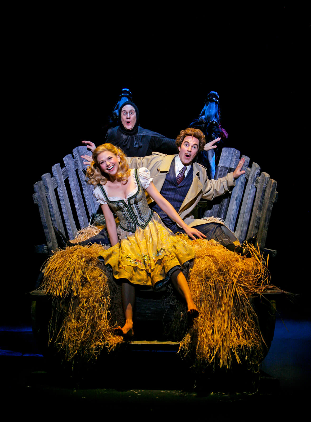 """Igor (Chris Fitzgerald), Dr. Frankenstein (Roger Bart) and Inga (Sutton Foster) singing """"Roll in the Hay"""". They are sitting a hay stack and rocking back and forth. Two horses rock up and down."""