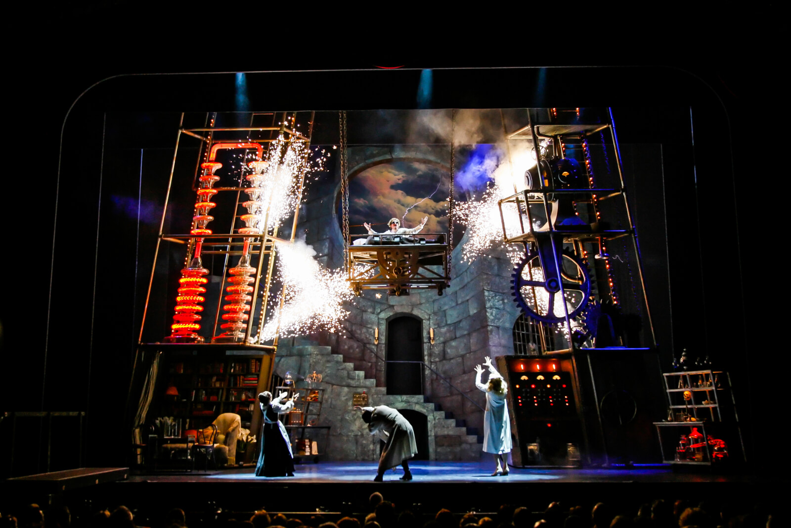 """Dr. Frankenstein (Roger Bart) sings """"Life, Life"""", in the lab. He is high in the air with the Monster laying on the lab table, below is Frau Blucher (Andrea Martin), Igor (Chris Fitzgerald ) and Inga (Sutton Foster). They are surrounded by electricity and sparks."""