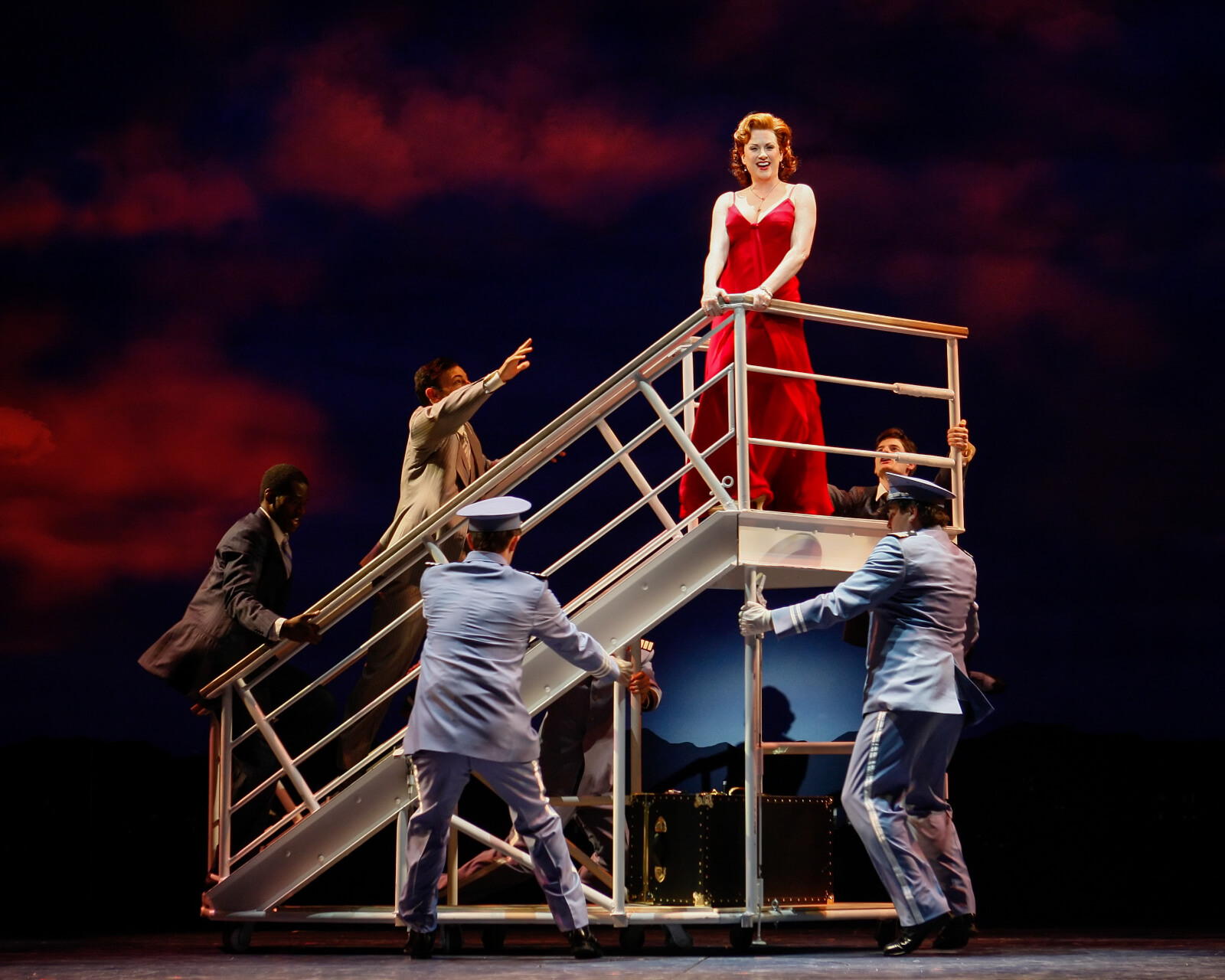 """Elizabeth (Megan Mullally) sings """"Please Don't Touch Me"""" at the ships pier. She is standing on a rolling stair unit and is surrounded by the crew from the ship."""