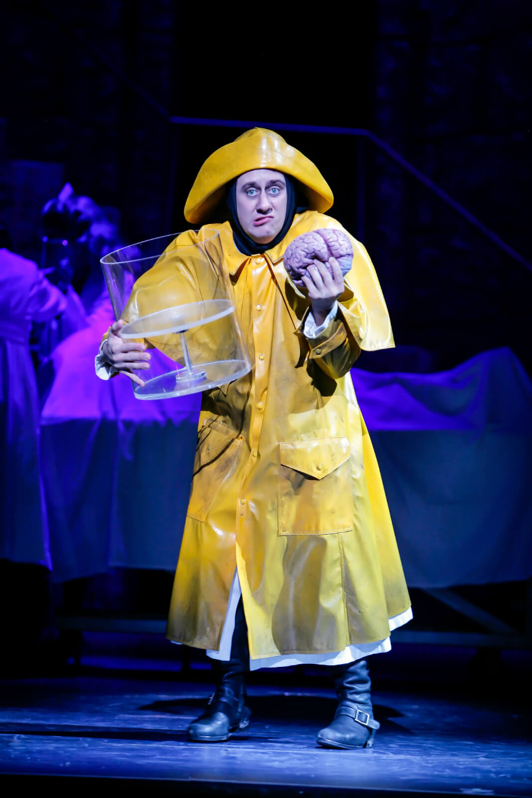Igor (Chris Fitzgerald) in a yellow rain coat, holding a human brain. He is stealing the brain from the brain depository.