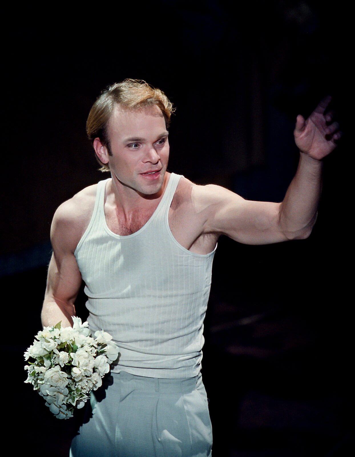 Camille Raquin (Norbert Leo Butz) in a white top, holding a small bouquet of white flowers